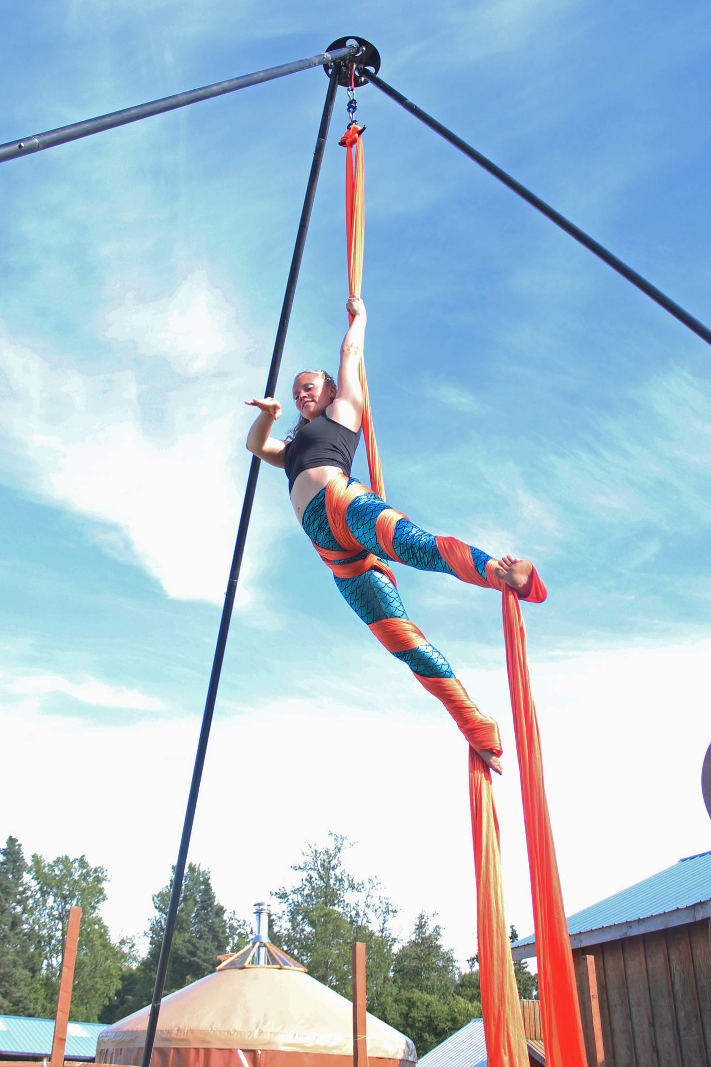 An aerial performer spins in the air next to the Ocean State at this year's Salmonfest on Saturday, Aug. 4, 2018 at the Kenai Peninsula Fairgrounds in Ninilchik, Alaska. (Photo by Megan Pacer/Homer News)