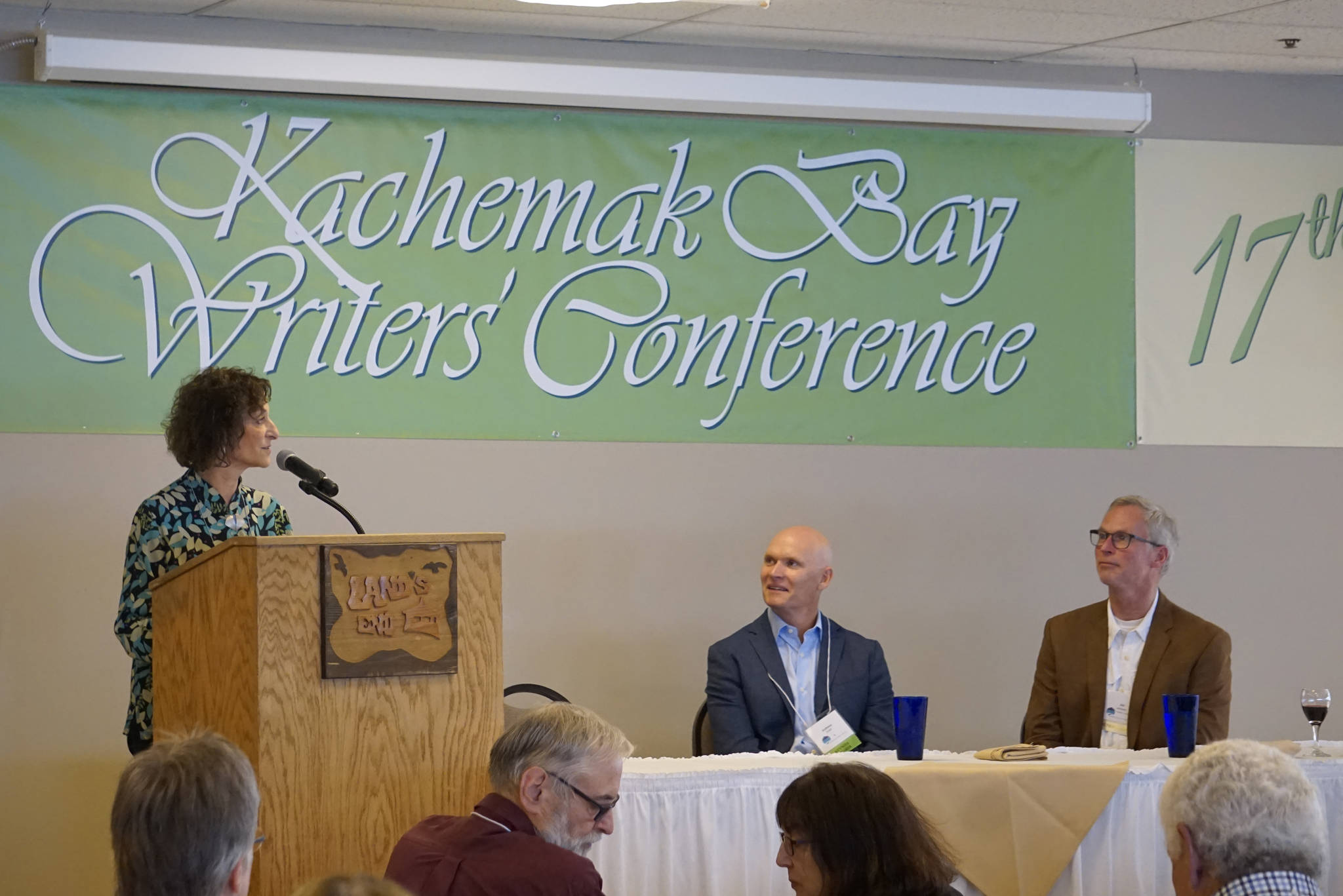 Kachemak Bay Campus Director Carol Swartz, left, speaks June 8, 2018, at the opening of the 2018 Kachemak Bay Writers' Conference at Land's End Resort in Homer, Alaska. (Photo by Michael Armstrong/Homer News)