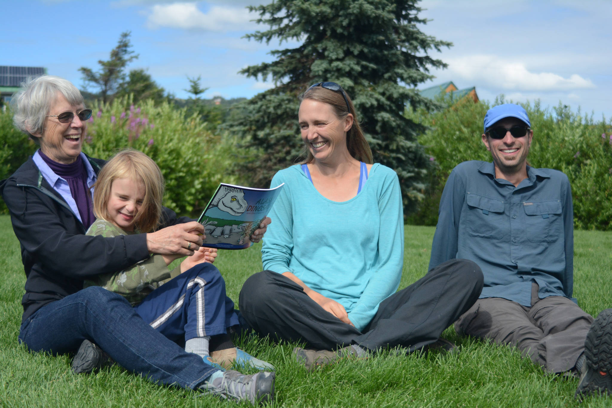 """Janet Klein, left, holds her grandson, Sylas Reising, 4, while she visits with her daughter, Deborah Klein, center, and son-in-law George Reising, right, at Bishop's Beach, Homer, Alaska, on Aug. 9, 2018. Not shown is Kai Reising, 6. Silas and Kai were the inspiration for the Klein's """"color and learn"""" book, """"Alaska's Dinosaurs and Other Cretaceous Creatures."""""""