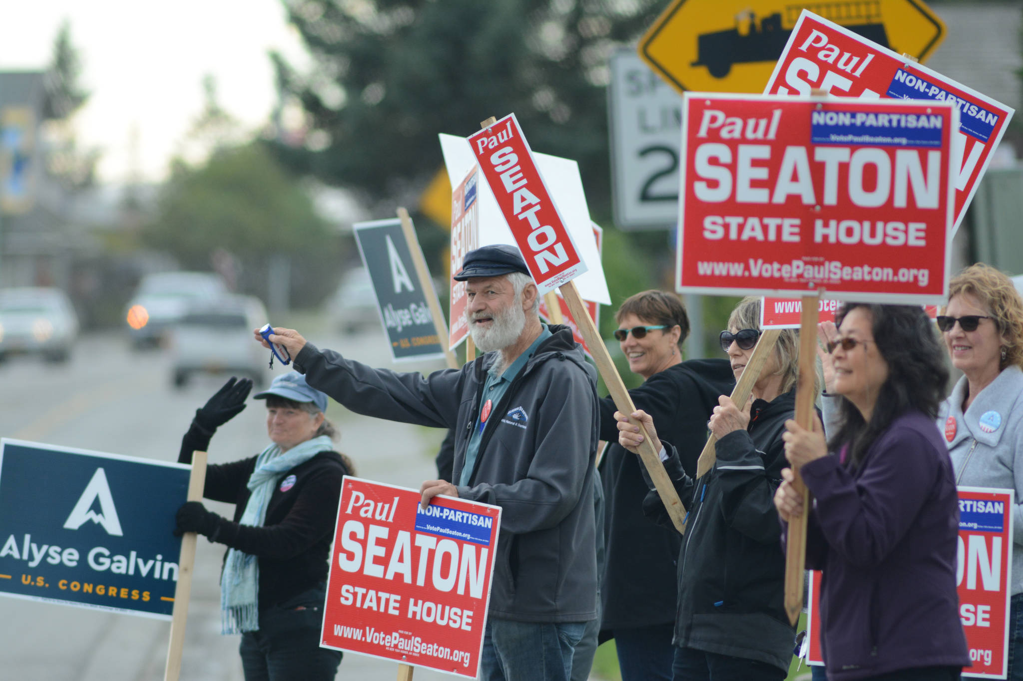 Rep. Paul Seaton, NP-Homer, center, is joined by supporters waving signs on primary election day, Aug. 21, 2018, at the corner of Lake Street and Pioneer Avenue in Homer. Seaton ran unapposed as a nonpartisan candidate for the Alaska Democratic Party seat. Also waving signs are supporters of Alyse Galvin, a nonpartisan candidate for the Democratic Party seat for U.S. Congress. (Photo by Michael Armstrong/Homer News)