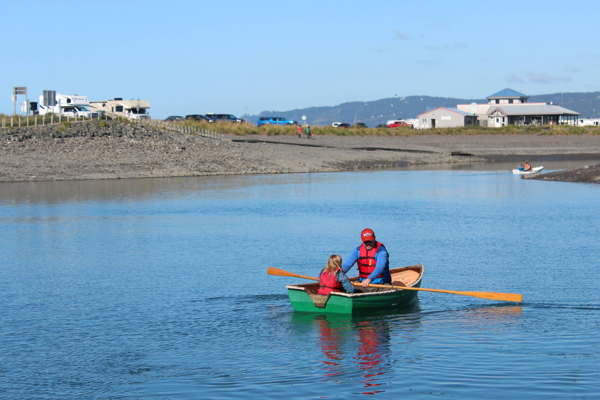 A man rows a young girl around the Nick Dudiak Fishing Lagoon in a wooden boat Saturday, Sept. 1, 2018 during the Kachemak Bay Wooden Boat Festival on the Homer Spit in Homer, Alaska. (Photo by Megan Pacer/Homer News)