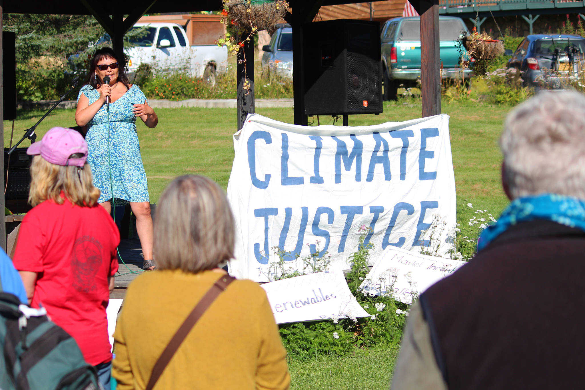 Area residents listen to Lydia Olympic, who worked with The Wilderness Society as a tribal advocate, as she gives a short speech Saturday, Sept. 8, 2018 at the Rise for Climate, Jobs and Justice rally and march at WKFL Park in Homer, Alaska. The local event, which ended in a march down to Mariner Park, was part of a larger movement of rallies held nationally on Sept. 8. (Photo by Megan Pacer/Homer News)