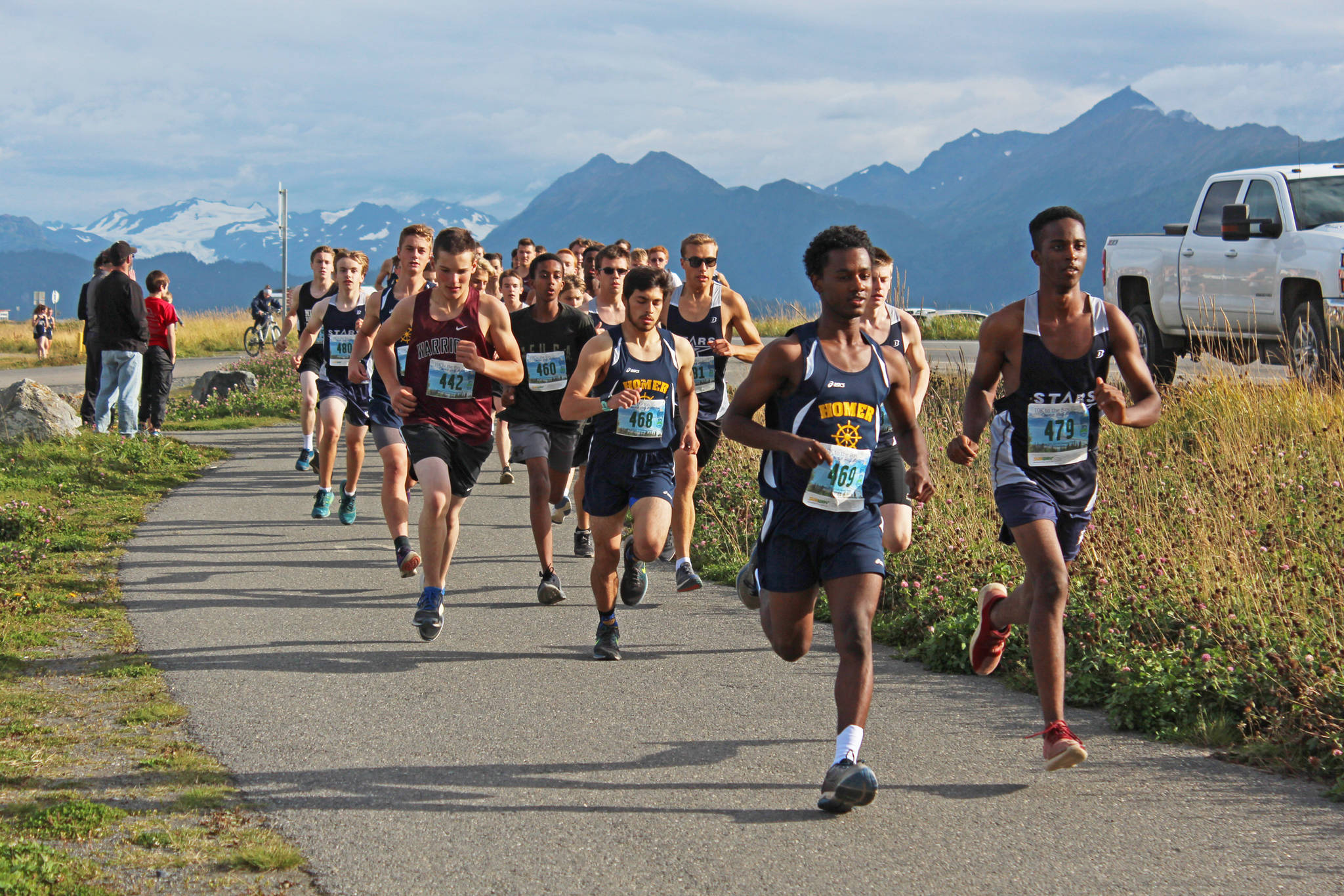 Cross-country runners take off from the starting line of the boys 5K Spit Run during the Homer Invitational on Friday, Sept. 7, 2018 on the Homer Spit in Homer, Alaska. The Soldotna boys team took first place, beating the Homer boys team by four points. (Photo by Megan Pacer/Homer News)