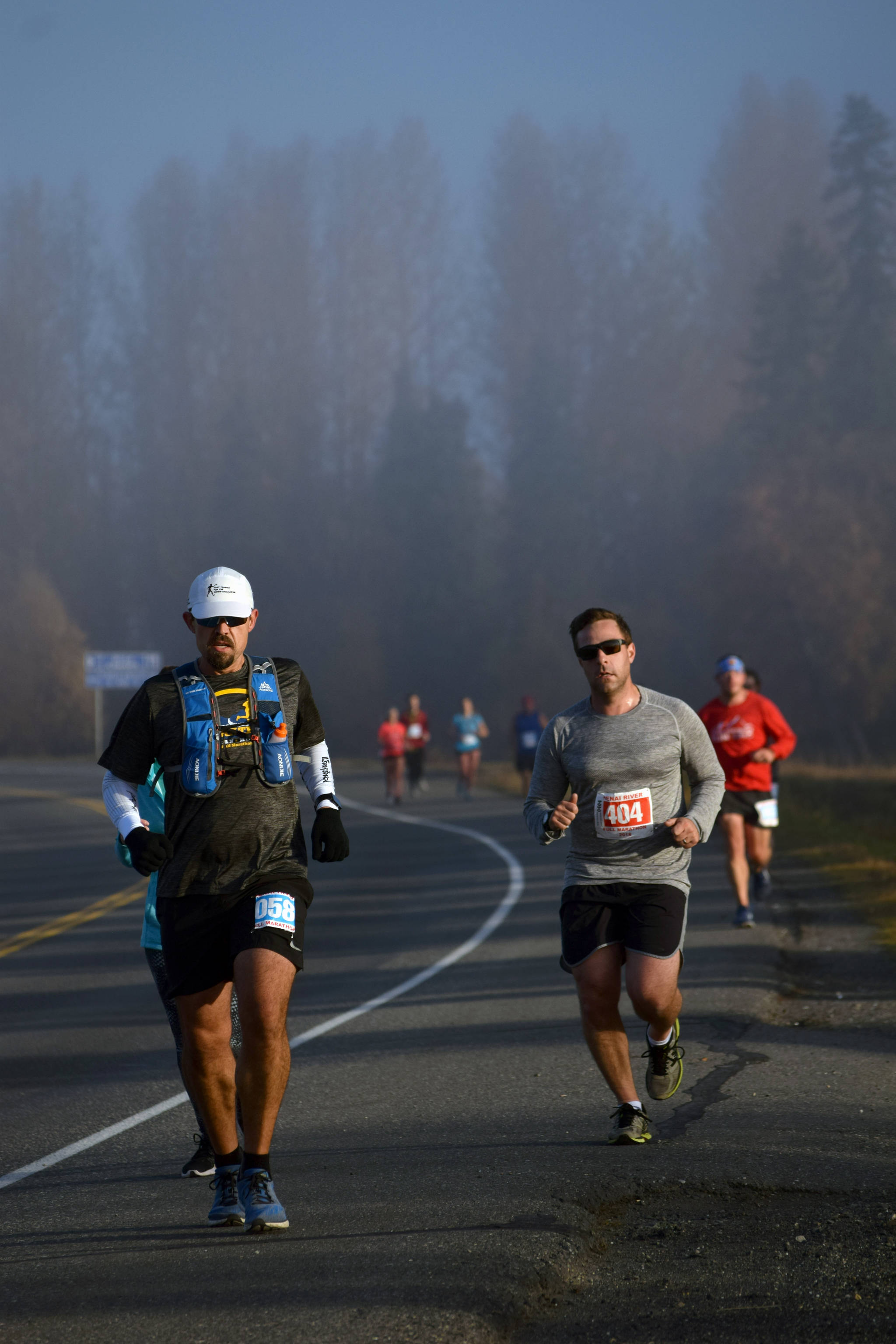 Michael Eriks of Carterville, Illinois, leads a pack of Kenai River Marathon racers through the early morning fog on Sunday, Sept. 30, 2018, on Bridge Access Road. (Photo by Jeff Helminiak/Peninsula Clarion)
