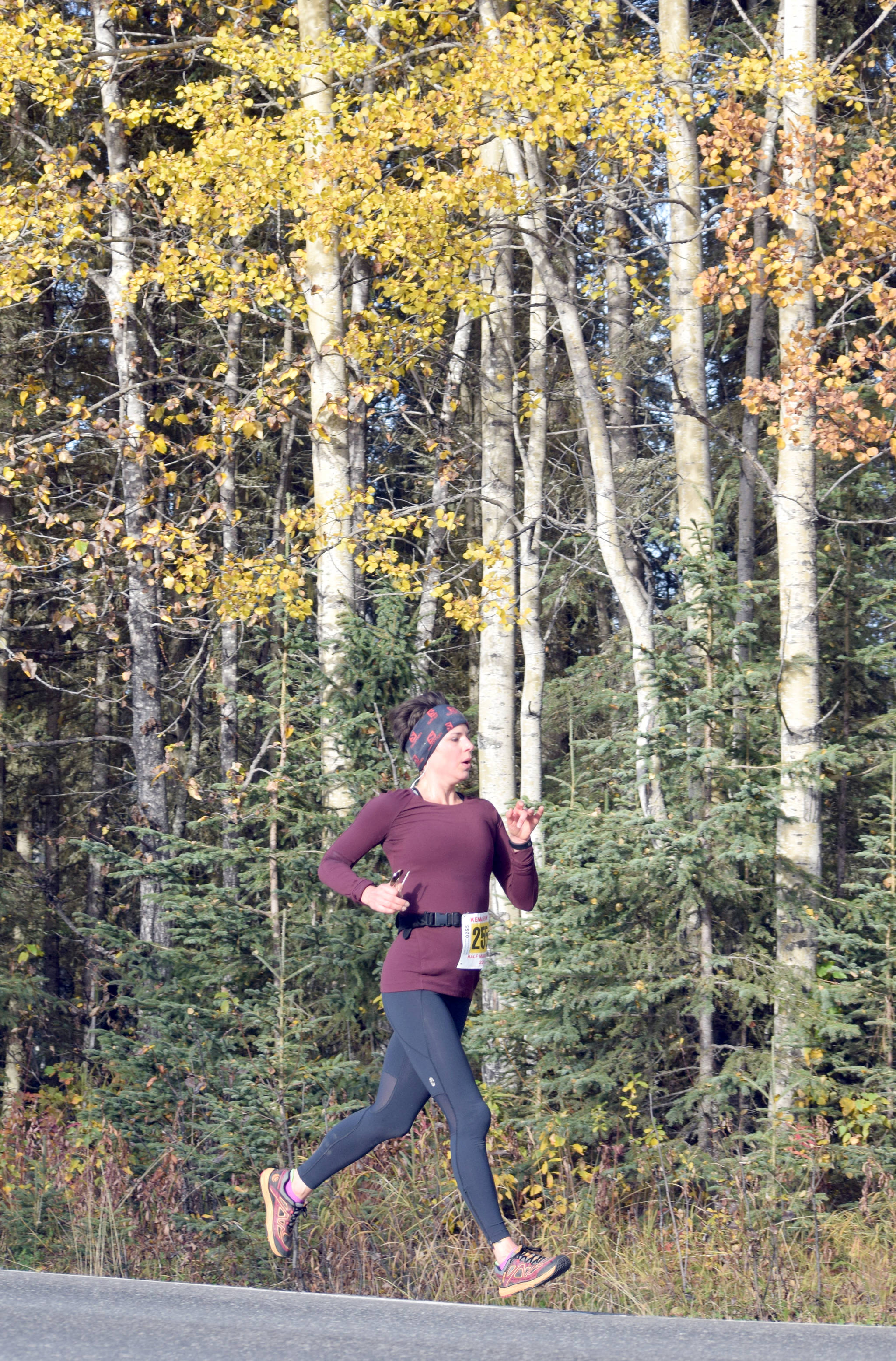 Eagle River's Victoria Oxetenko floats down Beaver Loop Road on the way to victory in the half marathon of the Kenai River Marathon on Sunday, Sept. 30, 2018. (Photo by Jeff Helminiak/Peninsula Clarion)