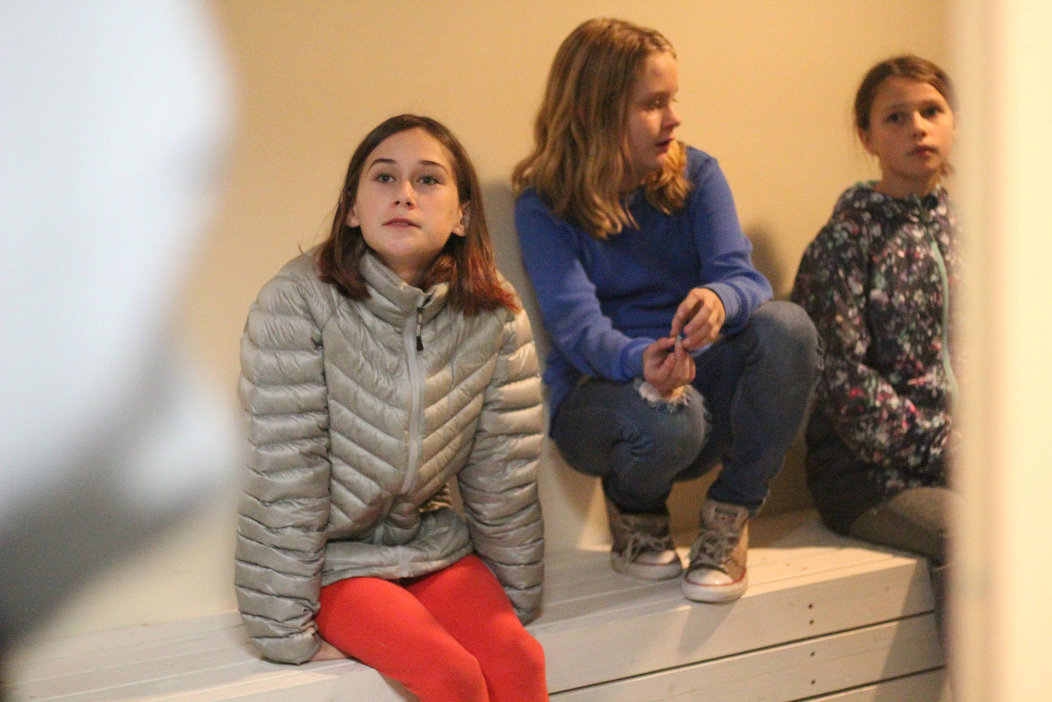 Thea James, Emma Macauly and Natalia Sherwood listen to information about a holding cell while they explore it at the Homer Courthouse on Oct. 8, 2018 in Homer, Alaska. The Fireweed Academy students and their classmates took a field trip to the courthouse to learn more about its inner workings and the law. (Photo by Megan Pacer/Homer News)