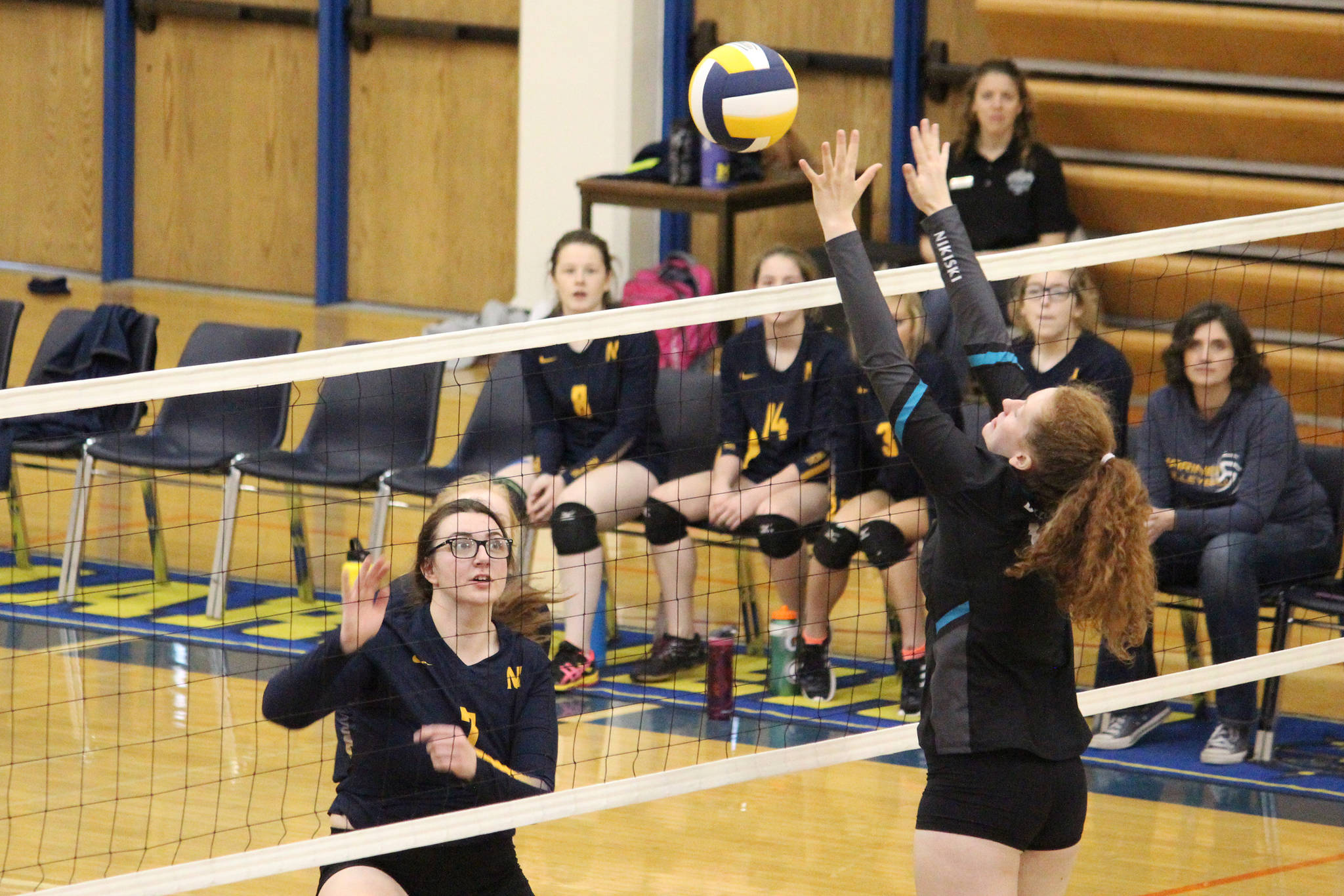 Nikiski's Kaycee Bostic jumps to block a hit from Homer's Tonda Smude during their game Saturday, Oct. 13, 2018 at the Alice Witte Gymnasium in Homer, Alaska. (Photo by Megan Pacer/Homer News)