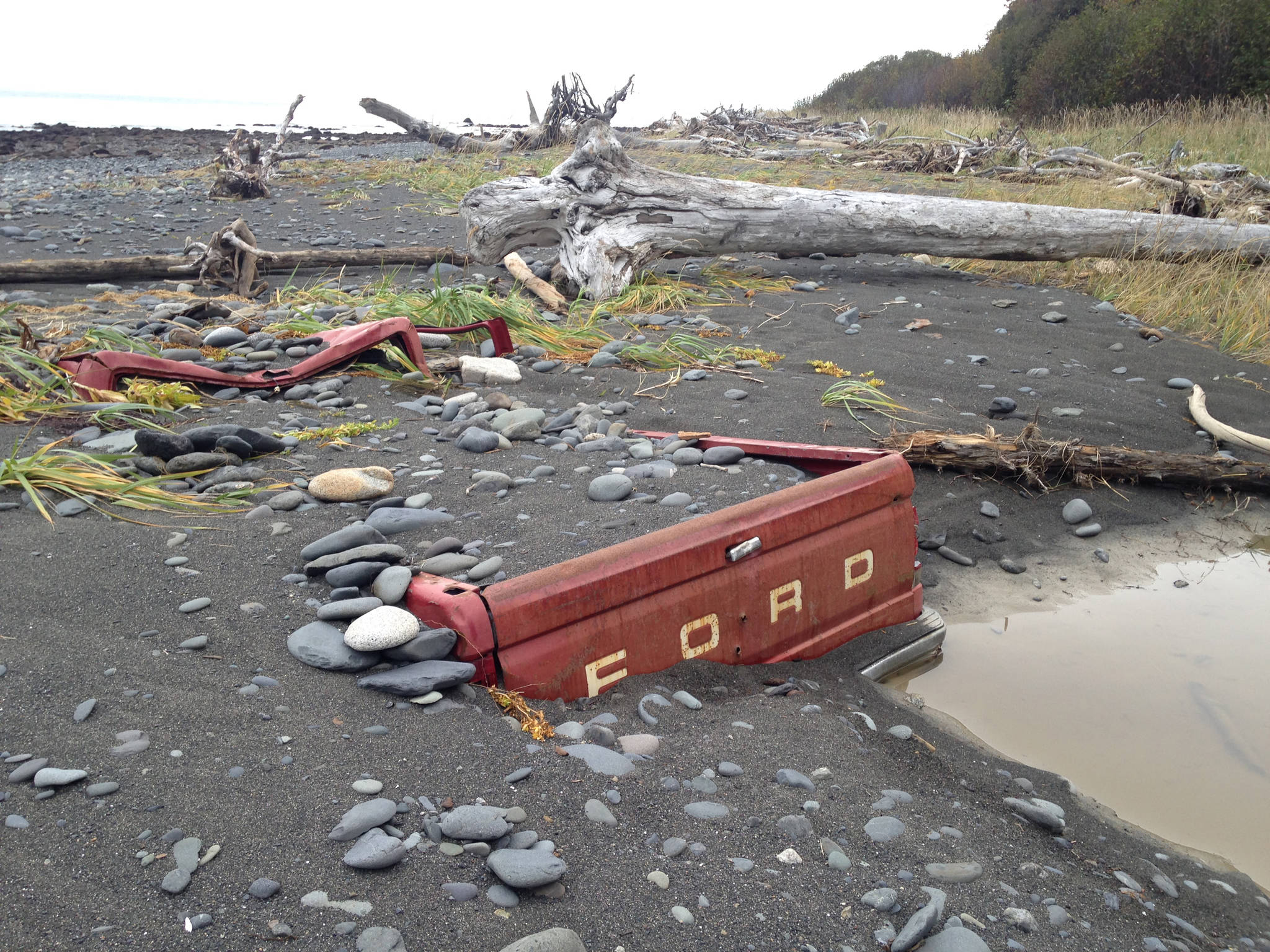 Storm tides have almost totally buried a Ford F-150 pickup truck on the beach south of Diamond Creek in this photo taken on Sunday, Oct. 14, 2018, near Homer, Alaska. The truck was abandoned on the beach in October 2011 and had then been on its tires. (Photo by Michael Armstrong/Homer News)