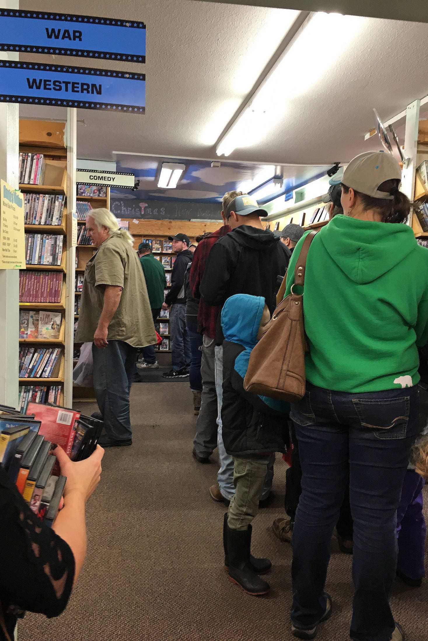 Customers form a line stretching from the register to the back of Barb's Video and DVD on Saturday, Oct. 20, 2018 in Homer, Alaska during the movie rental store's first day of its merchandise sale. (Photo by Megan Pacer/Homer News)