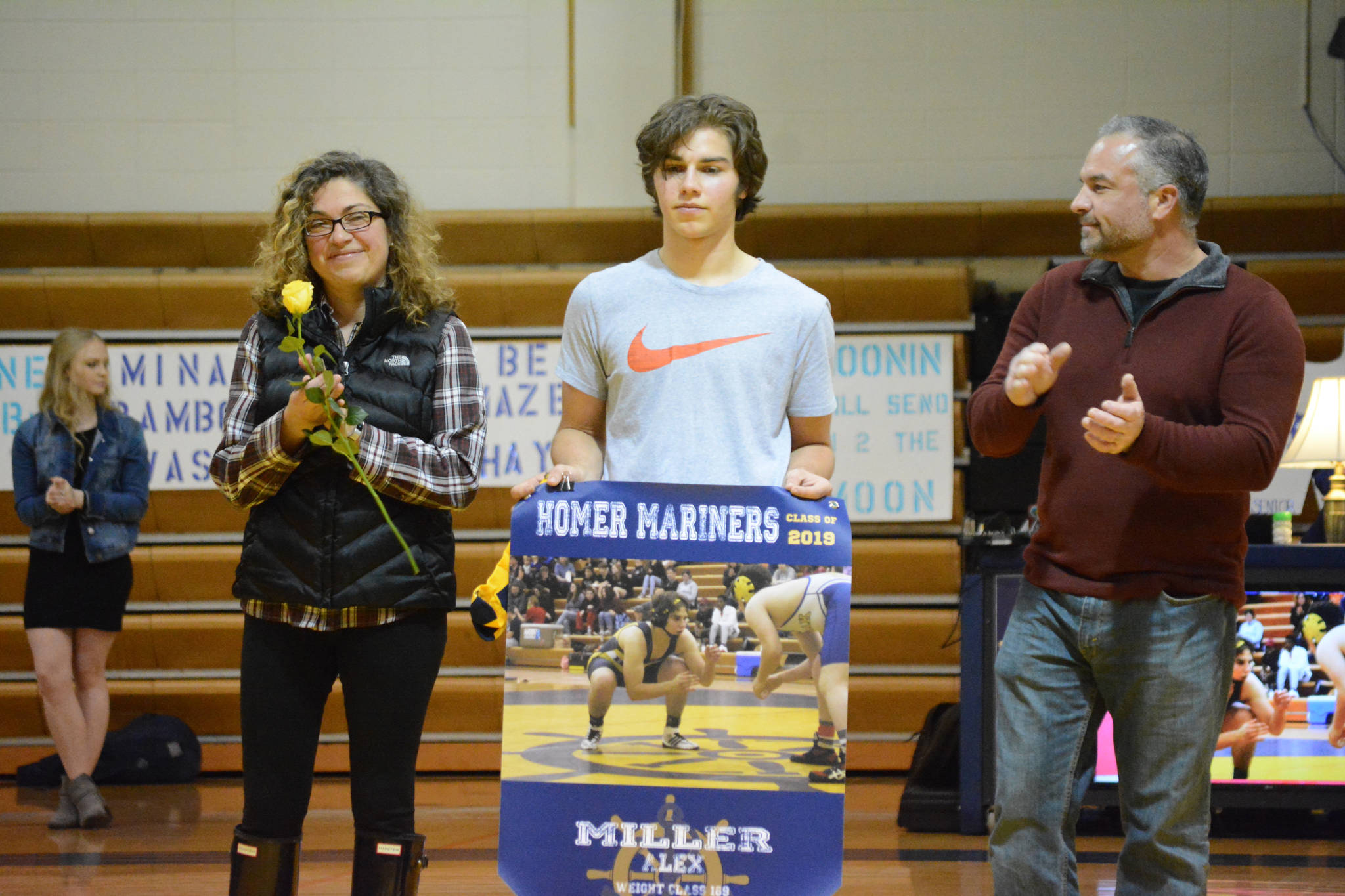 Alex Miller, center, holds a banner recognizing him at Senior Night, the Homer-Kenai dual wrestling meet held Nov. 21, 2018, in the Homer High School Alice Witte Gym, Homer, Alaska. His mother, Loreta Miller, left, and father, Brian Miller, clap for their son. (Photo by Michael Armstrong/Homer News)