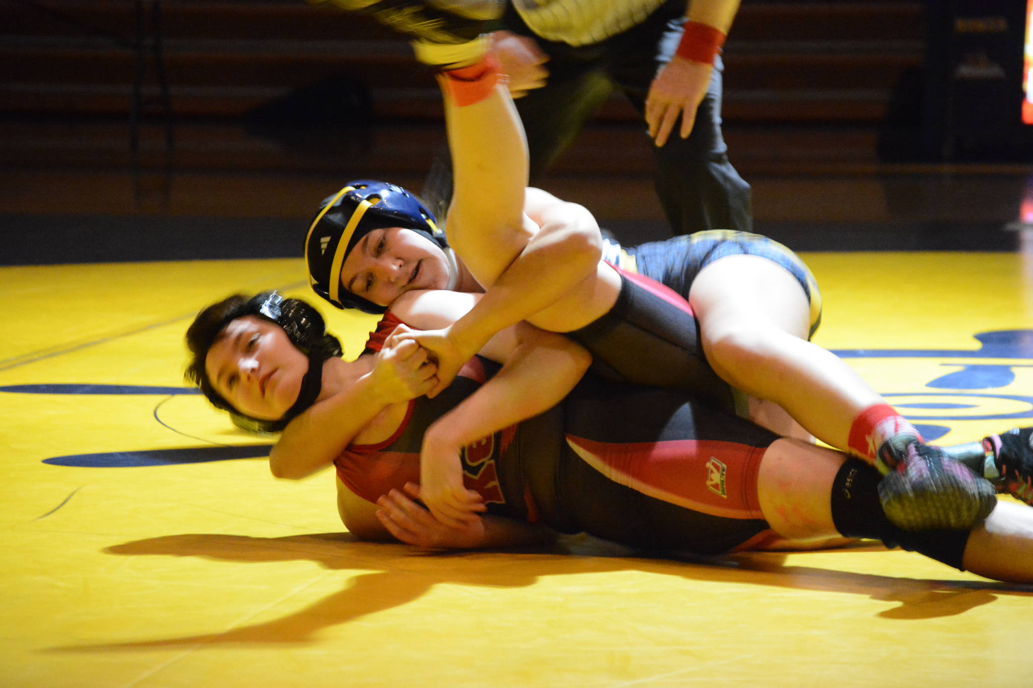 Homer High School Mariner Mina Cavasos, top, wrestles with Kenai High School Kardinal Olivia Easley,bottom, in an exhibition meet held Wednesday, Nov. 21, 2018, at the Homer High School Alice Witte Gym in Homer, Alaska. (Photo by Michael Armstrong/Homer News)