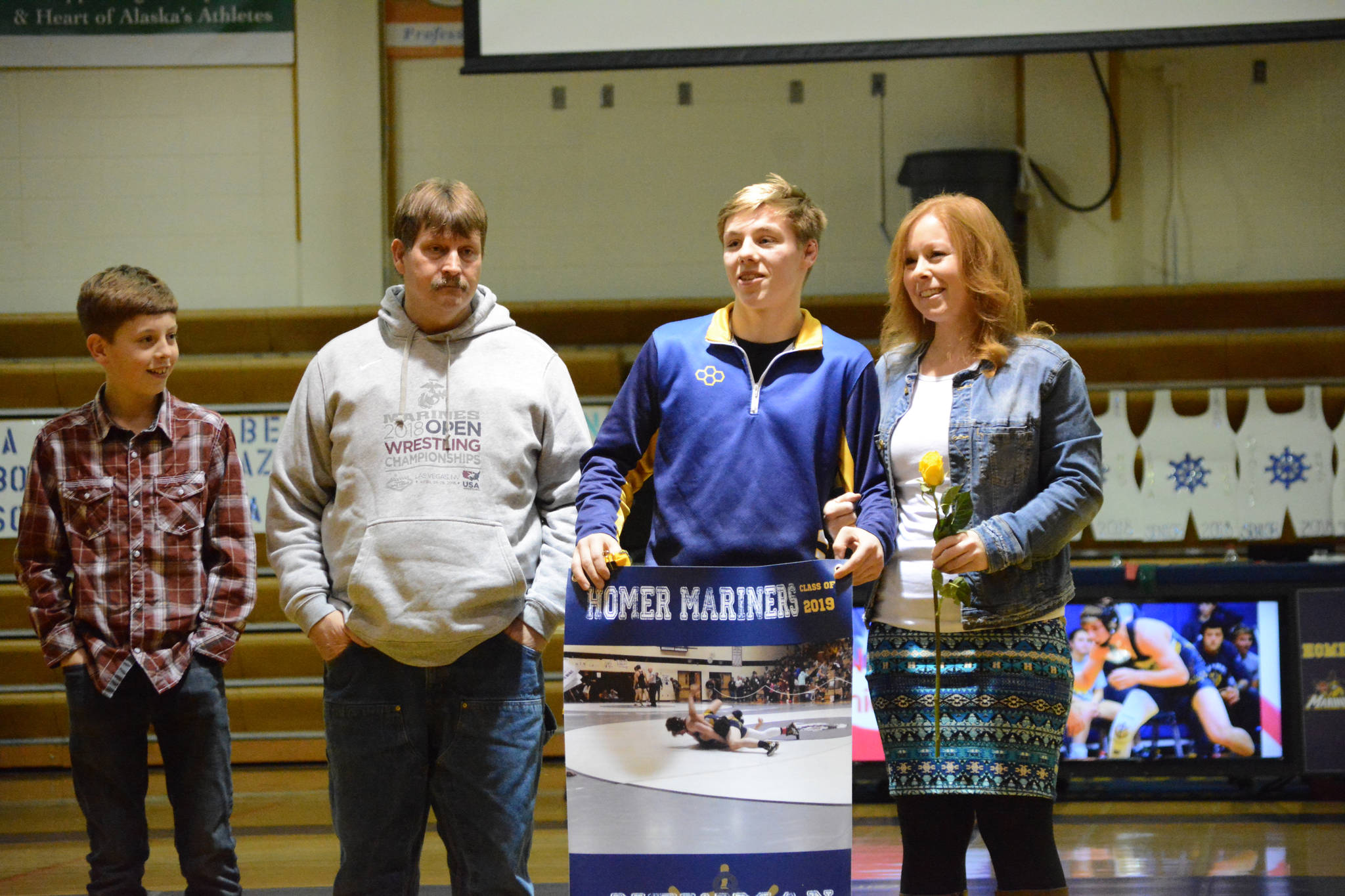 Wayne Newman holds a banner recognizing him at Senior Night, the Homer-Kenai dual wrestling meet held Nov. 21, 2018, in the Homer High School Alice Witte Gym, Homer, Alaska. Supporting him are his parents, Sam and Auriell Newman, and brother, ??? Newman. (Photo by Michael Armstrong/Homer News)