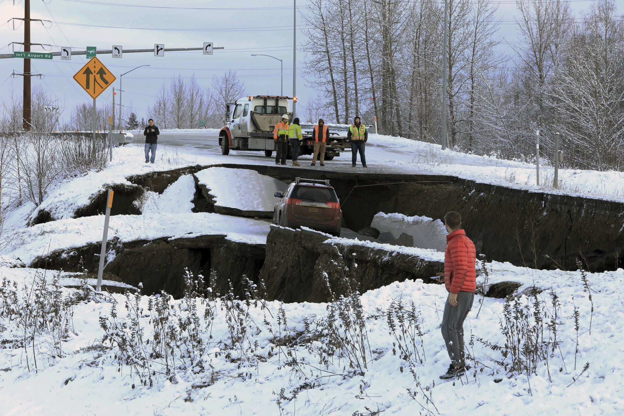 Highway workers and spectators look at a car stuck on a section of an off-ramp that collapsed during an earthquake Friday morning, Nov. 30, 2018 in Anchorage, Alaska. The driver was not injured attempting to exit Minnesota Drive at International Airport Road. Back-to-back earthquakes measuring 7.0 and 5.8 rocked buildings and buckled roads Friday morning in Anchorage, prompting people to run from their offices or seek shelter under office desks, while a tsunami warning had some seeking higher ground. (Dan Joling | Associated Press)
