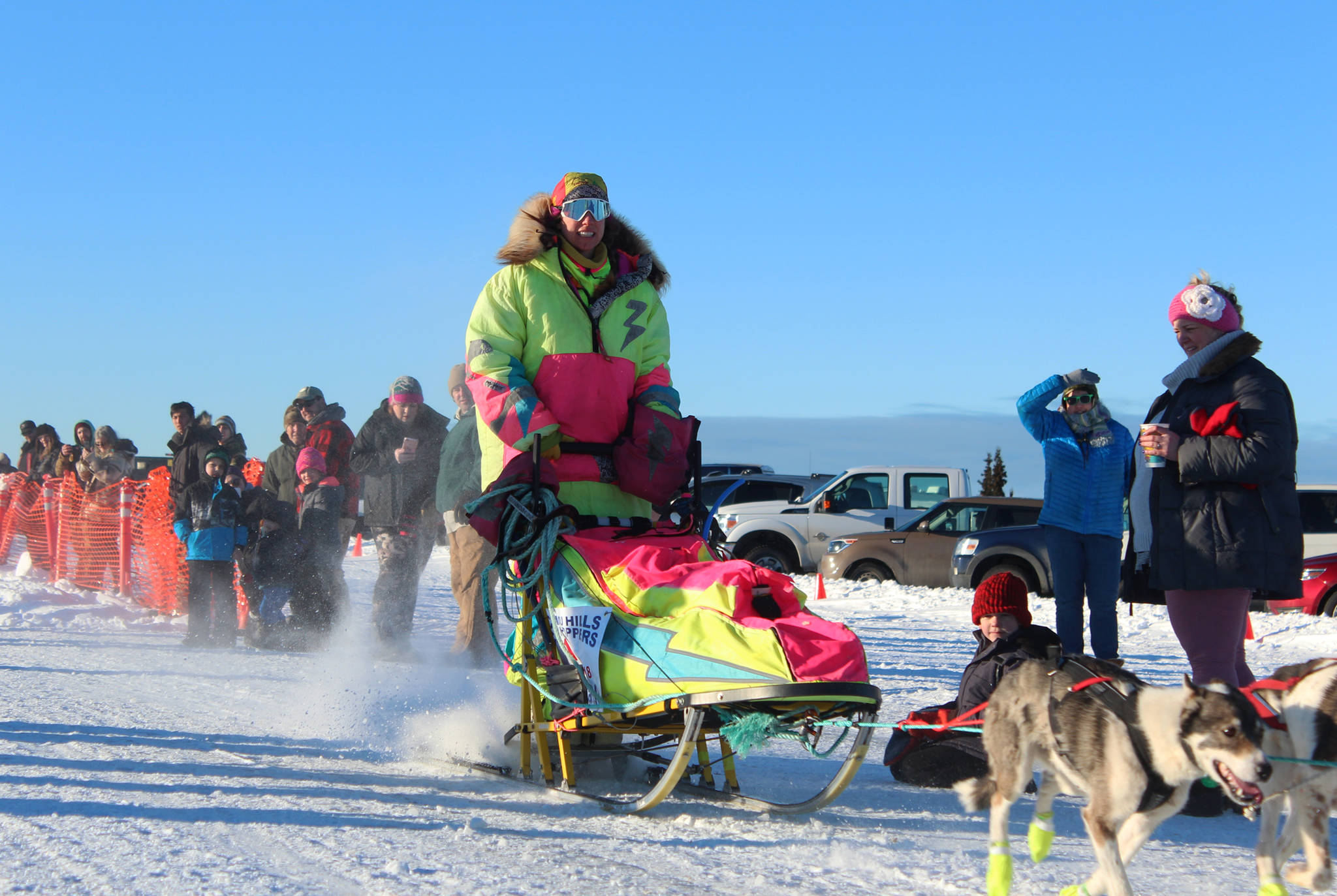 Monica Zappa, in her telltale neon garb, takes off with her team from the starting line of this year's Tustumena 200 Sled Dog Race on Saturday, Jan. 27, 2018 at Freddie's Roadhouse in Ninilchik, Alaska. (Homer News file photo)