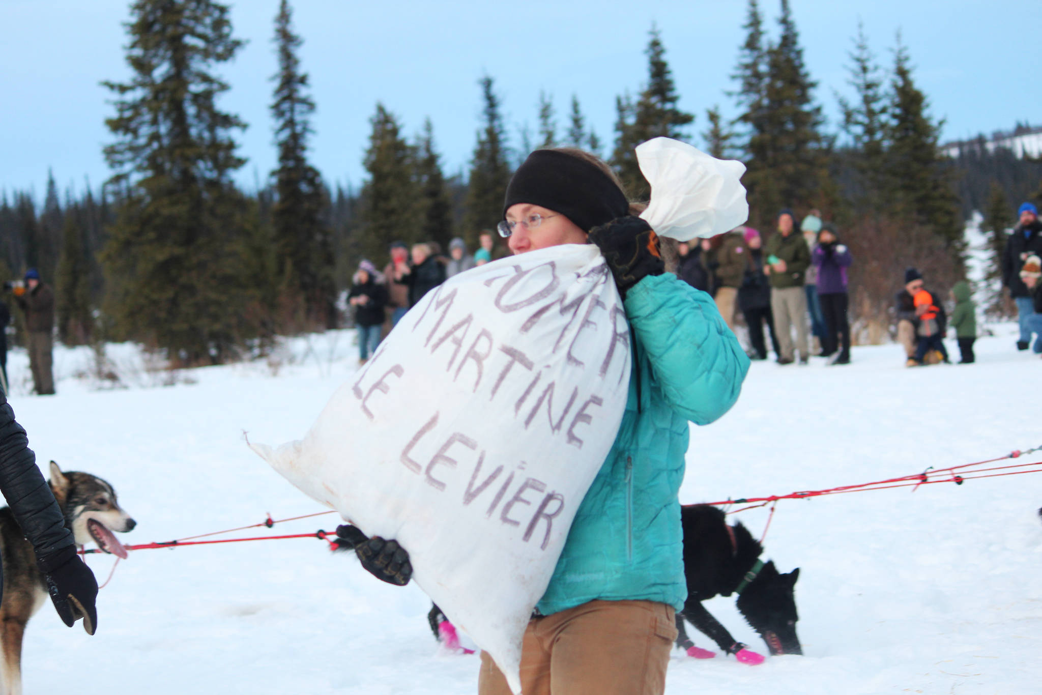 A volunteer carries a bag of supplies to one of the mushers in this year's Tustumena 200 Sled Dog Race while at the first checkpoint Saturday, Jan. 26, 2019 at McNeil Canyon Elementary School near Homer, Alaska. (Photo by Megan Pacer/Homer News)