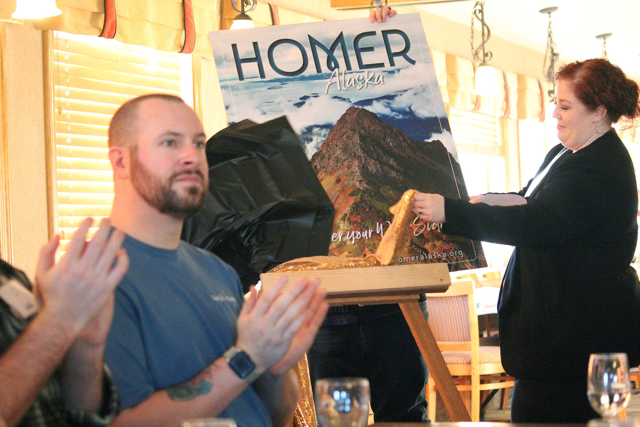 Homer Chamber of Commerce Executive Director Debbie Speakman unveils the winning photo that will grace the cover of the chamber's next visitor guide at a Tuesday, Jan. 15, 2019 annual chamber meeting at the Best Western in Homer, Alaska. Russel Campbell of Wandering Nomad Photography took the photo. (Photo by Megan Pacer/Homer News)