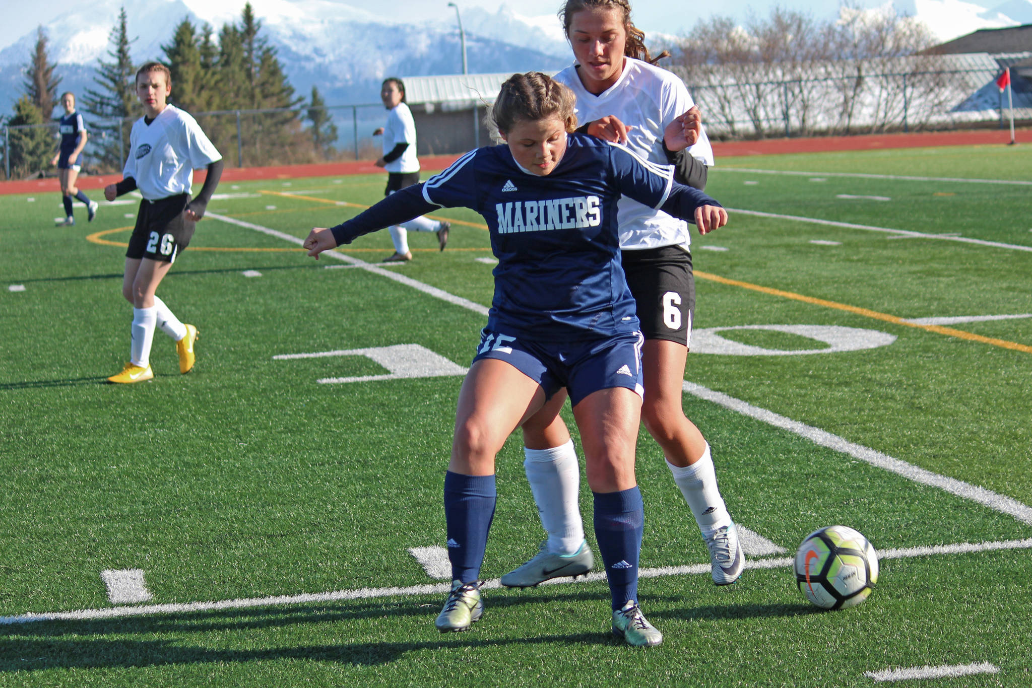 Homer's Rylee Doughty gets in front of Nikiski's Emma Wik while battling for the ball during a Tuesday, April 23, 2019 game at Homer High School in Homer, Alaska. (Photo by Megan Pacer/Homer News)