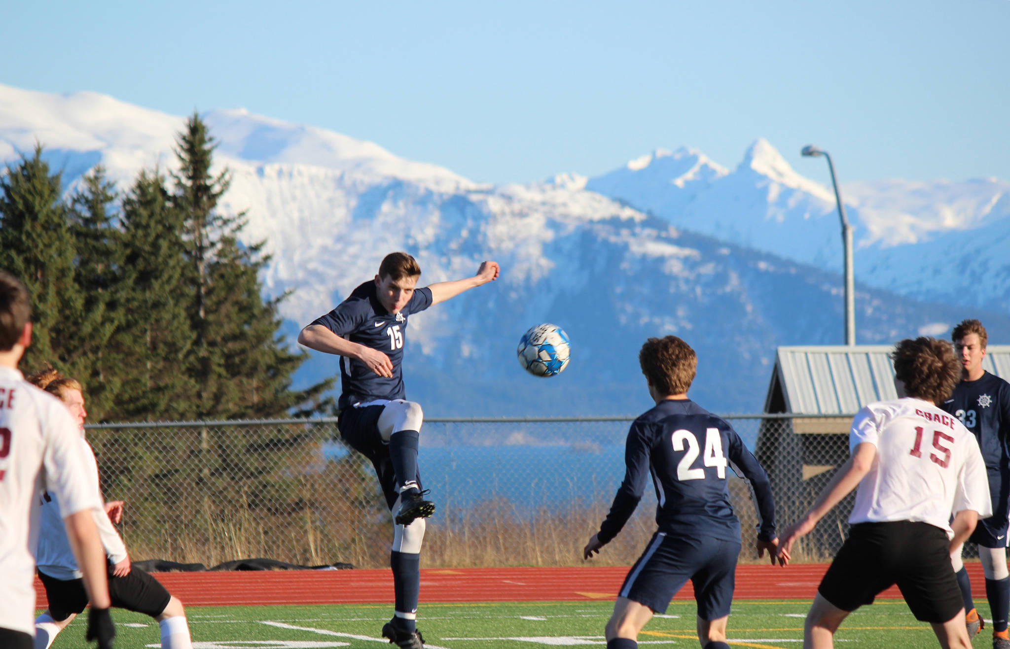 Homer Mariner Ethan Pitzman, 15, keeps the ball in play during Friday's game against Grace Christian, Friday, April 26, 2019, at the high school in Homer, Alaska while teammates Austin Shafford, 24, and Henry Russell, 33, keep the Grace Christian team at a distance. (Photo by McKibben Jackinsky)