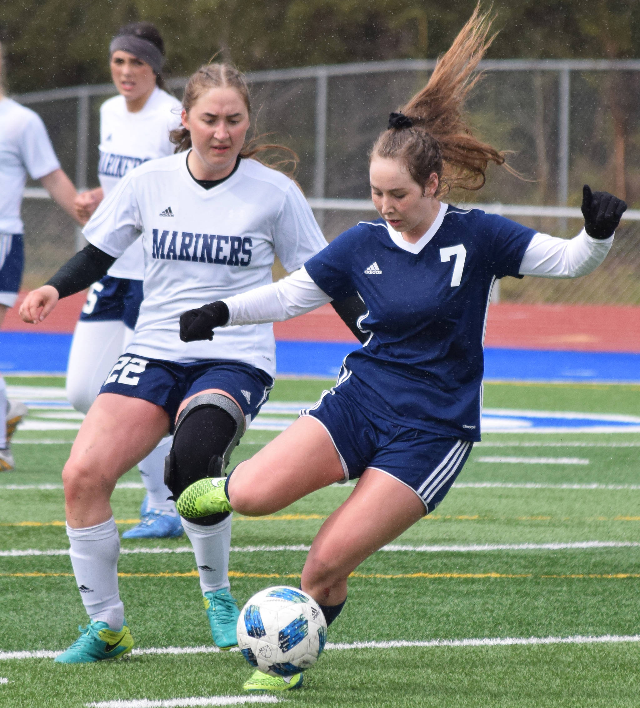Soldotna's Journey Miller (7) unleashes a kick in front of Homer's Brenna McCarron Saturday, May 11, 2019, in a Peninsula Conference game in Soldotna, Alaska. (Photo by Joey Klecka/Peninsula Clarion)