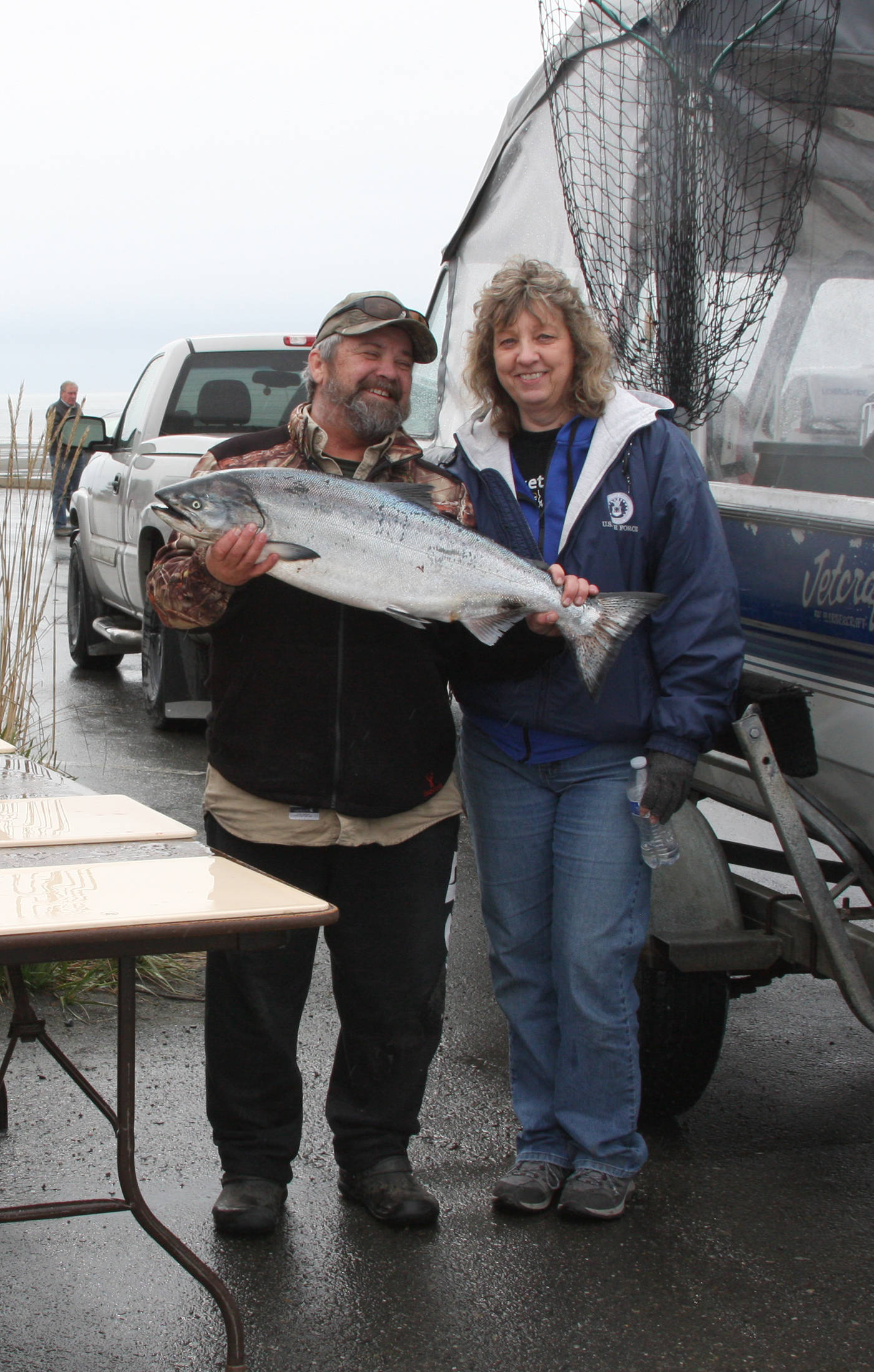 John and Yvonne Ketelle of Home pose with one of the two king salmon caught on their boat, Circus Circus, at the weigh-in station during the Anchor Point Calcutta on Sunday, May 12 in Anchor Point, Alaska. (Photo by Delcenia Cosman)