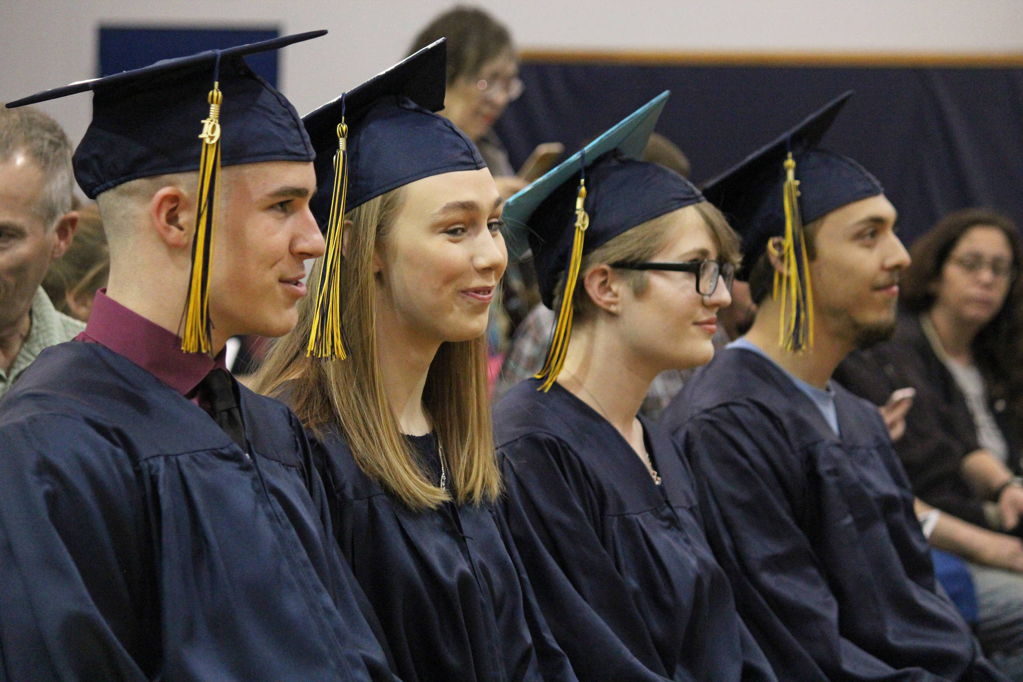 From left to right, the four 2019 Ninilchik School graduates: Garrett Koch, Isabella Koch, Tala Hadro and Jacob Shell listen during their graduation ceremony Tuesday, May 21, 2019 at Ninilchik School in Ninilchik, Alaska. (Photo by Megan Pacer/Homer News)