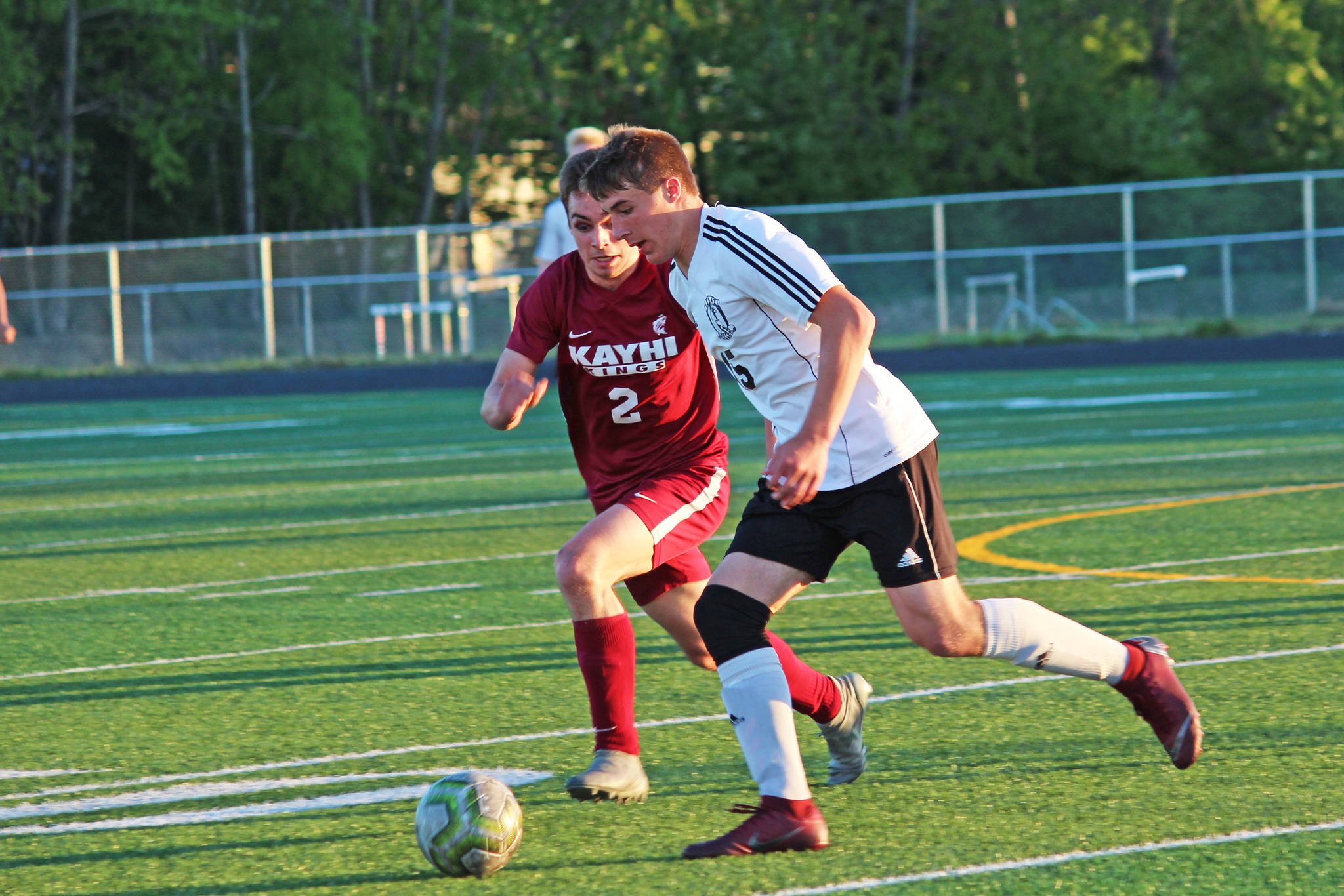 Ketchikan's Jake Taylor (left) and Kenai's Tucker Vann race to the ball during a Friday, May 24, 2019 semifinal match in the Division II state soccer championships at West Anchorage High School in Anchorage, Alaska. (Photo by Megan Pacer/Homer News)