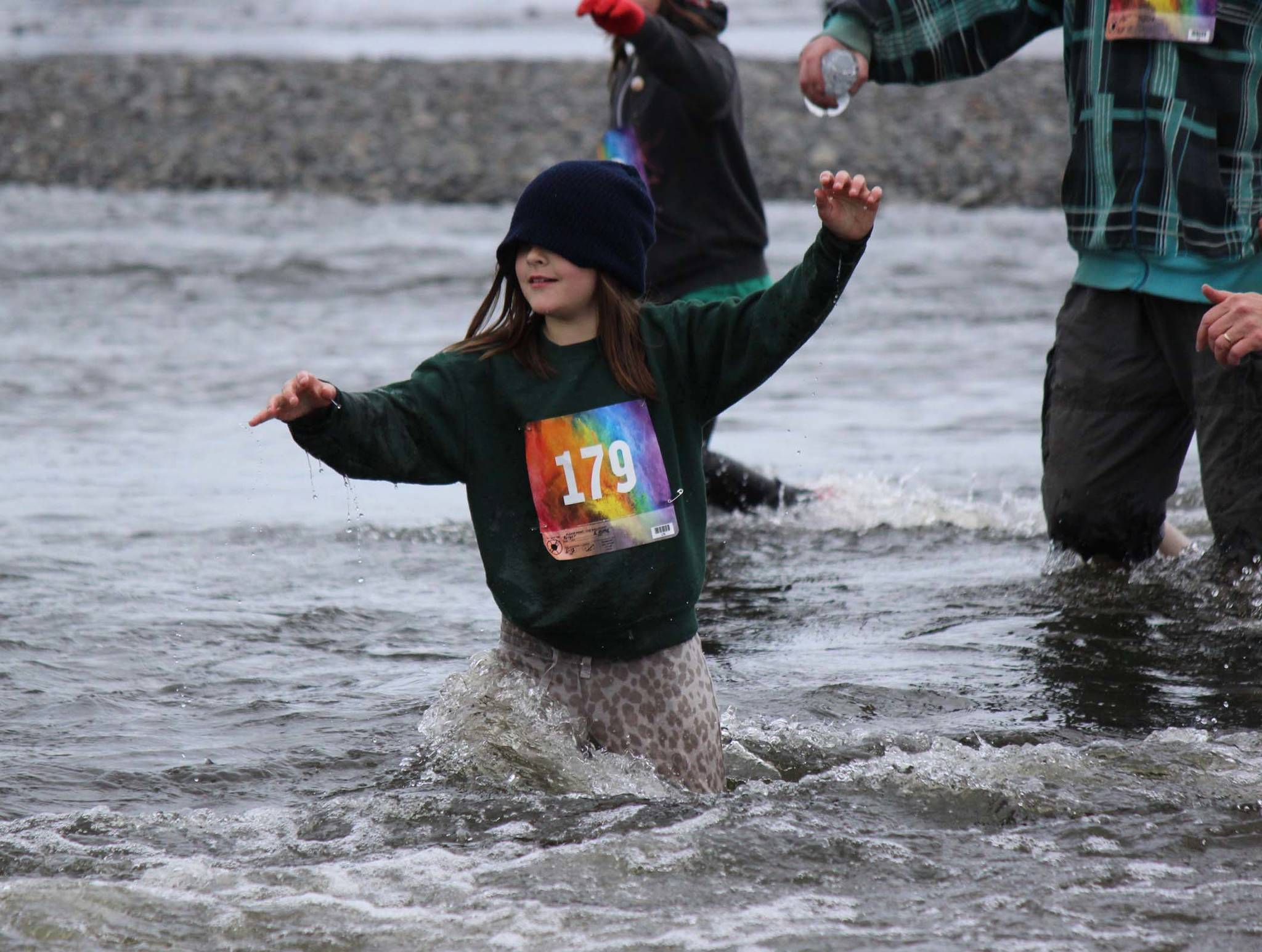 Unbothered by a drooping sweatshirt hood, Emma Berger, 179, relies on her feet to find a way across the gravel bottom of Deep Creek during the Clam Scramble held June 15, 2019 in Ninilchik, Alaska. (Photo by McKibben Jackinsky)