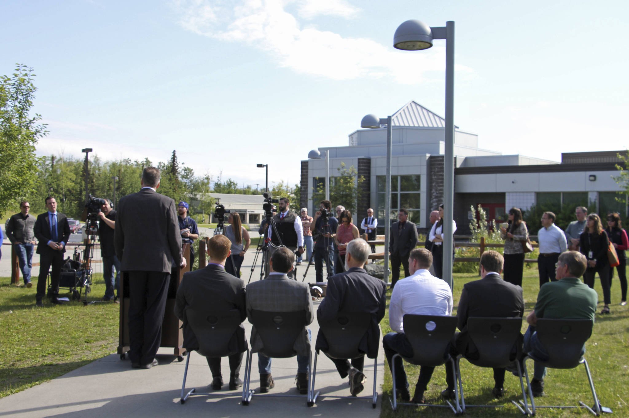 Alaska Gov. Mike Dunleavy, standing at podium, speaks at a news conference Friday, June 14, 2019, in Wasilla, Alaska. Dunleavy has called lawmakers into special session July 8 in Wasilla, and his administration gave a tour of the recommended site at Wasilla Middle School to reporters. (AP Photo/Mark Thiessen)