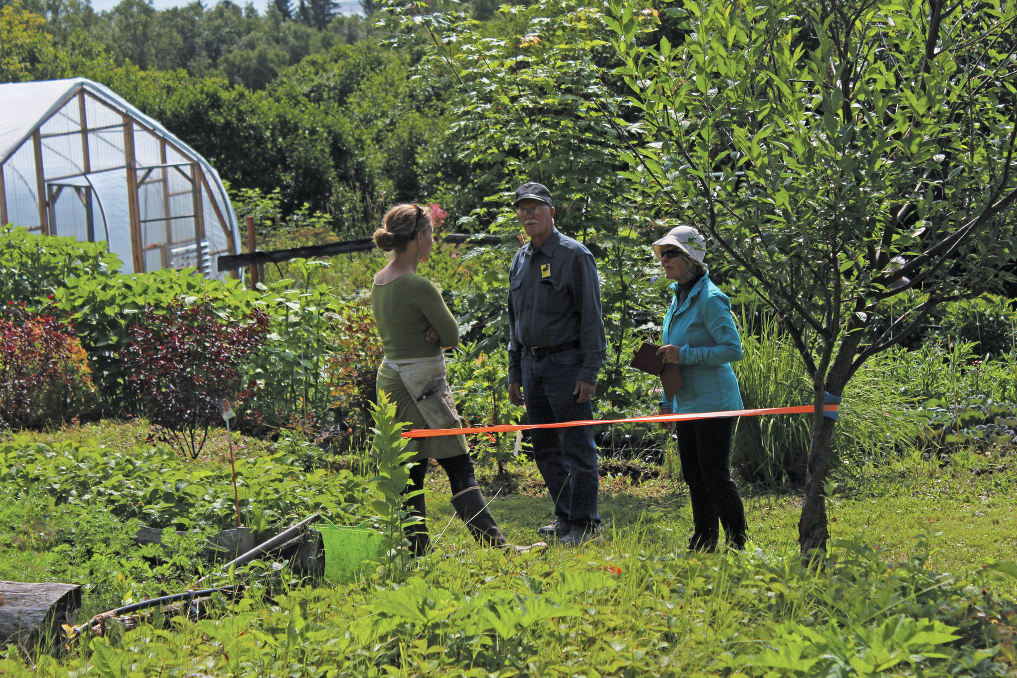 Visitors ask questions of Rachel Lord, who owns Alaska Stems, during this year's Garden Tour on Sunday, July 28, 2019 at her garden in Homer, Alaska. (Photo by Megan Pacer/Homer News)