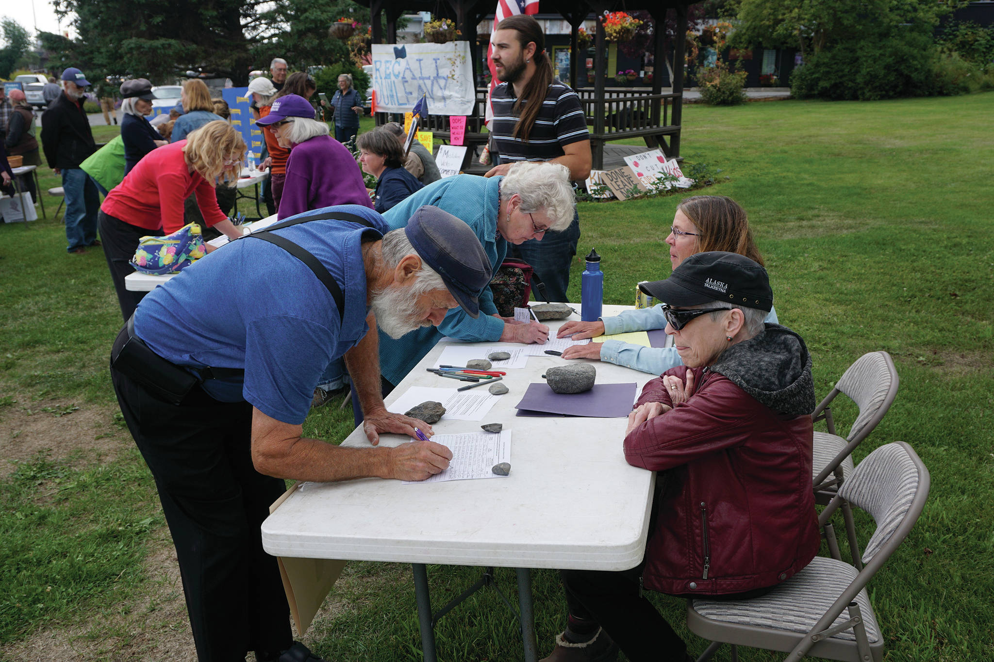 Recall Dunleavy organizers Ann Keffer, right, in hat, and Pat Cue, behind Keffer, take signatures at a Recall Dunleavy rally held on Aug. 1, 2019, at WKFL Park in Homer, Alaska. At left, former Homer Rep. Paul Seaton, NP-Homer, signs a form. Seaton lost to Rep. Sarah Vance, R-Homer, in the general election. (Photo by Michael Armstrong)
