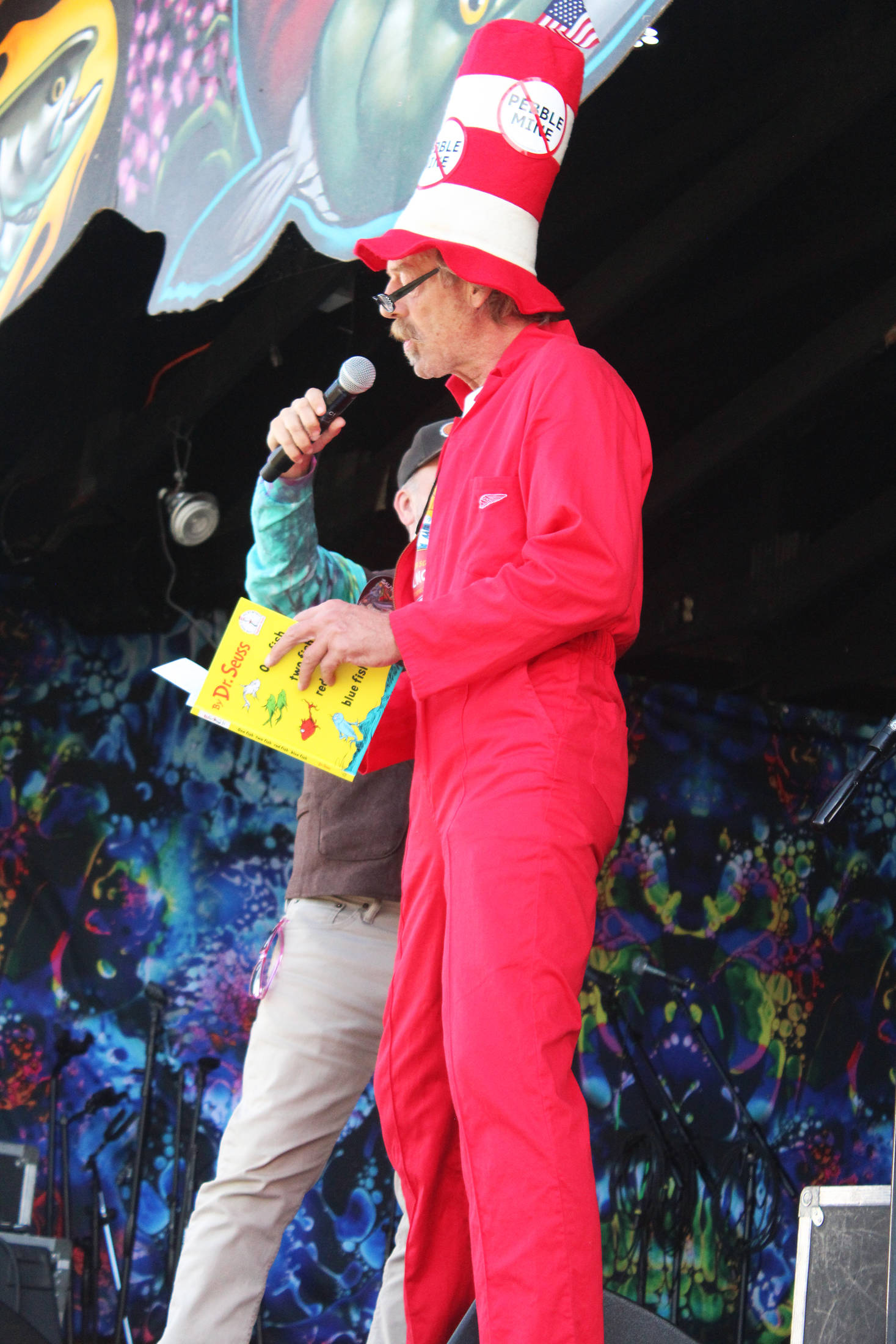 "Soldotna resident Daniel Lynch reads from the book ""One Fish, Two Fish, Red Fish, Blue Fish"" by Dr. Suess as part of a speech about the importance of protecting salmon habitat on Saturday, Aug. 3, 2019 at Salmonfest in Ninilchik, Alaska. (Photo by Megan Pacer/Homer News)"