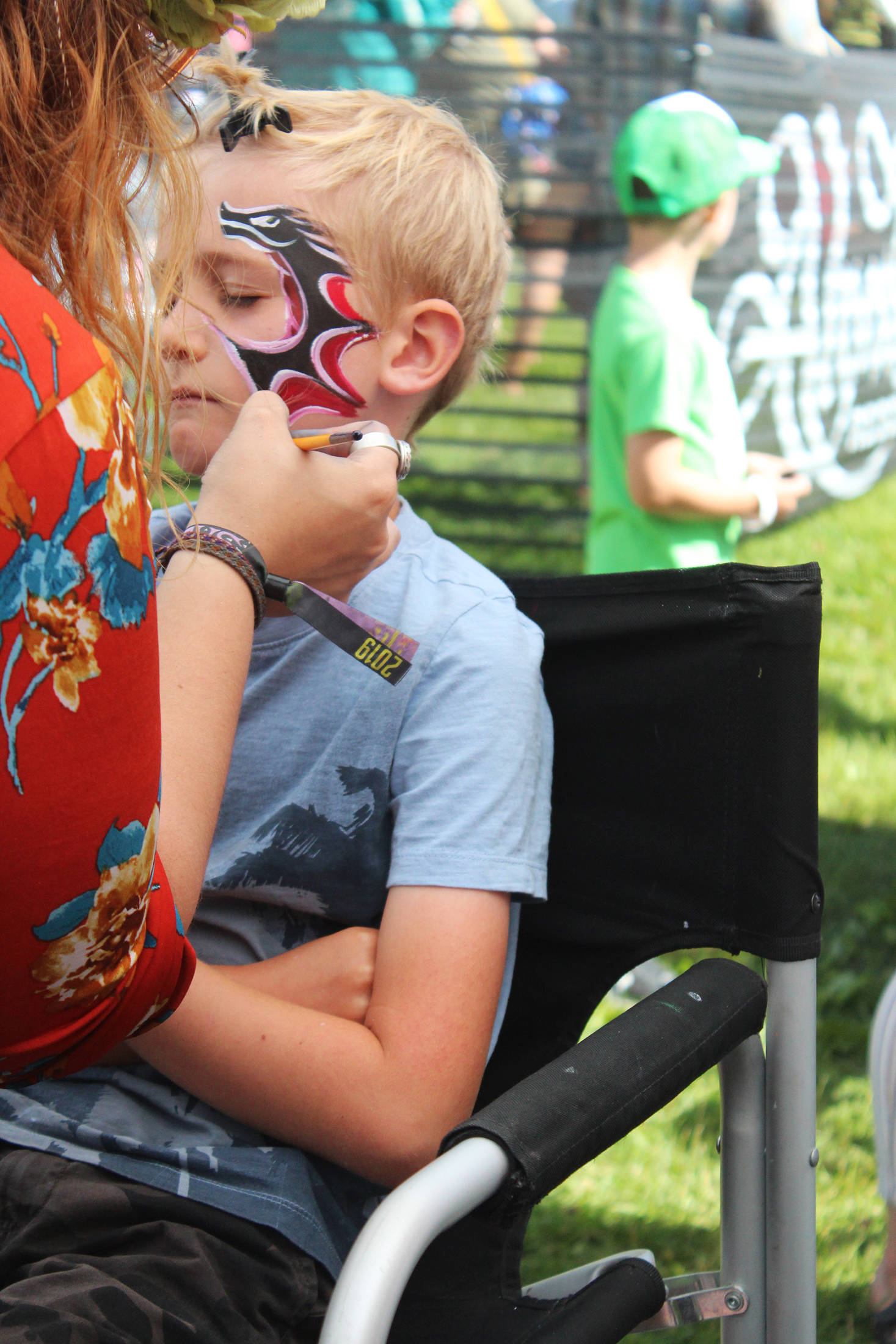Iver Ledahl, 8, of Kenai, gets his face painted on Friday, Aug. 2, 2019 at Salmonfest in Ninilchik, Alaska. (Photo by Megan Pacer/Homer News)