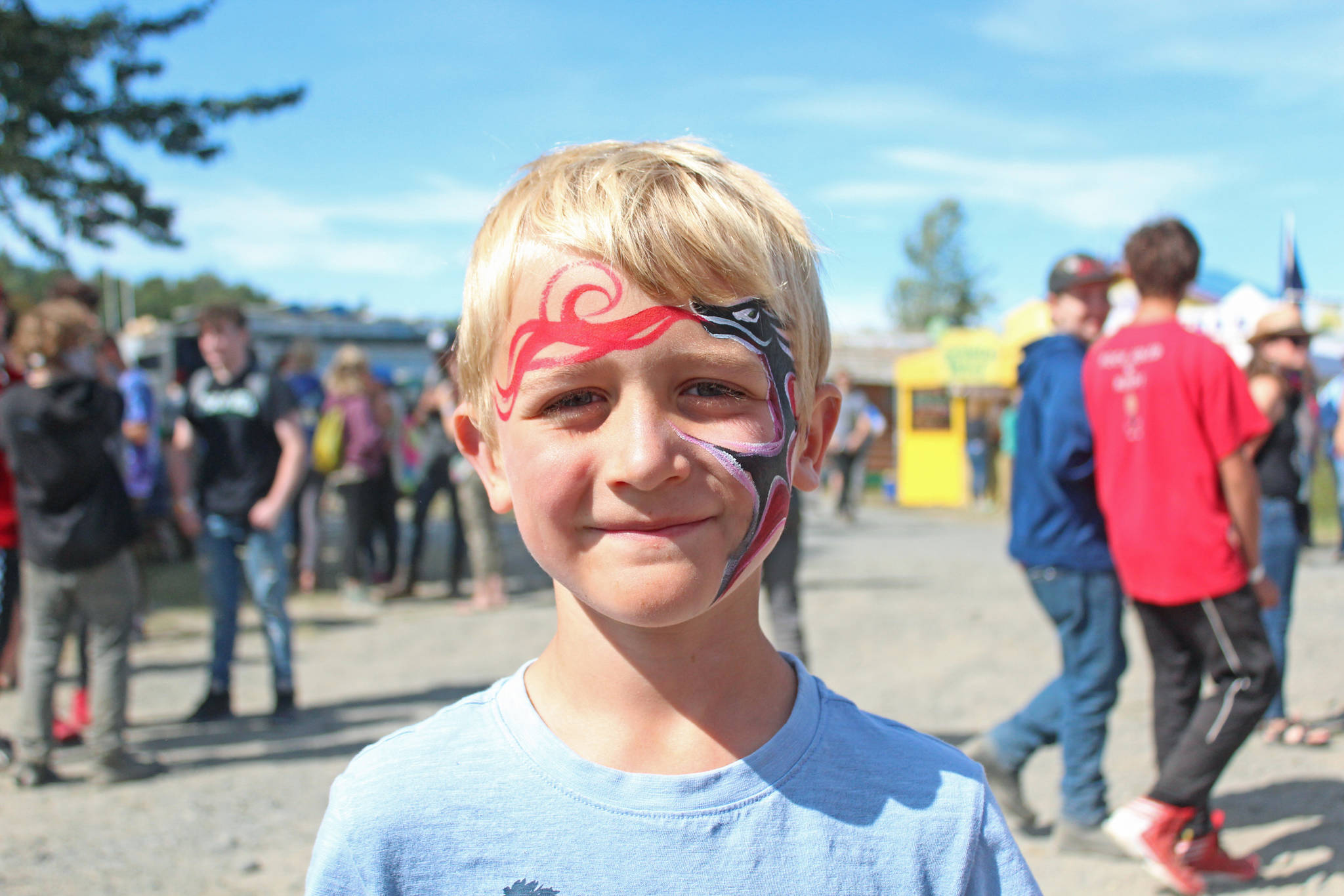 Iver Ledahl, 8, of Kenai, shows off the finished product of his face paint on Friday, Aug. 2, 2019 at Salmonfest in Ninilchik, Alaska. (Photo by Megan Pacer/Homer News)