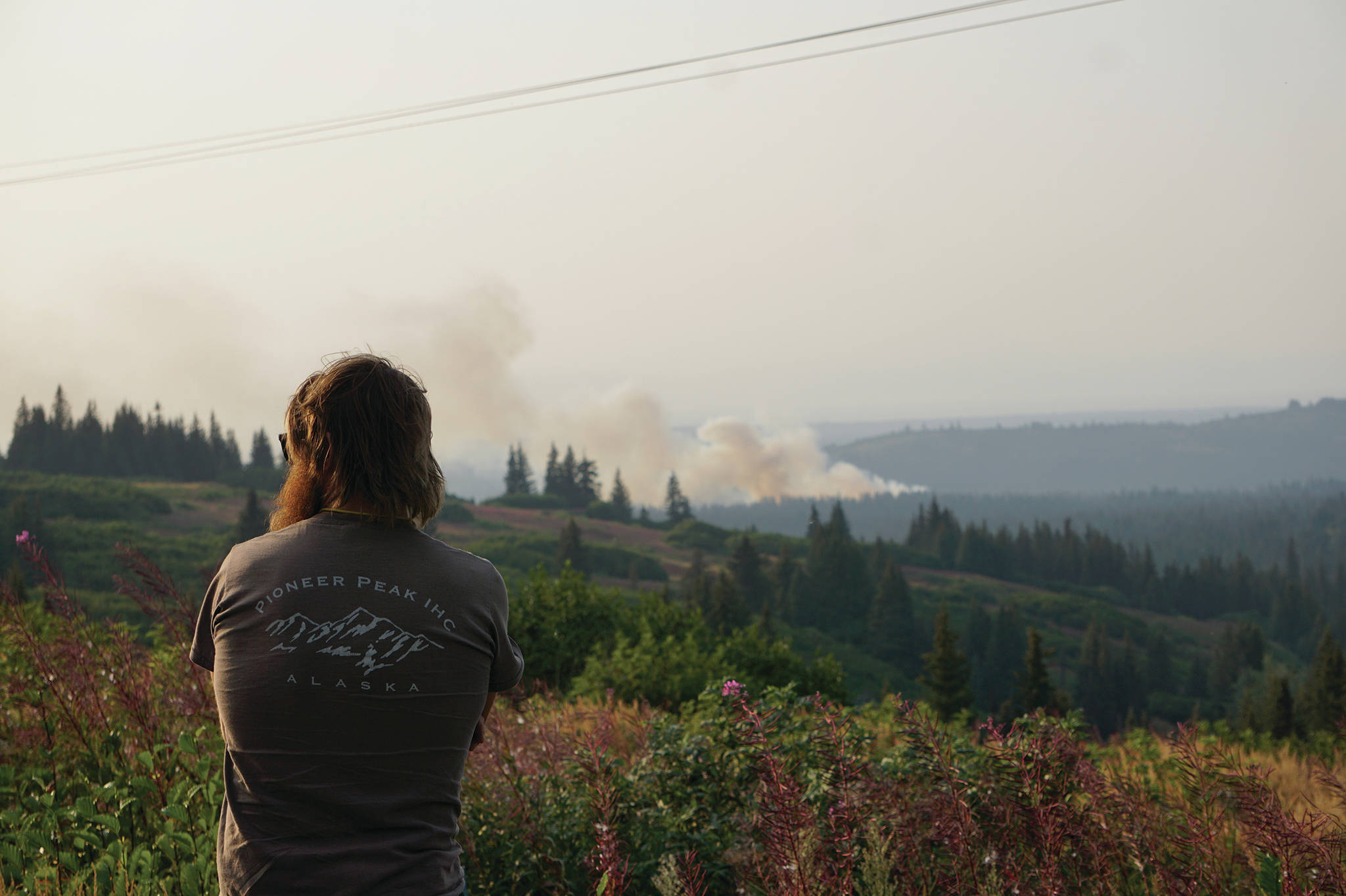 Diamond Ridge resident Parick Buongiorne watches the North Fork fire as it burns near the south end of the North Fork Road on Sunday evening, Aug. 18, 2019, near Homer, Alaska, as seen from Diamond Ridge Road. Buongiorne had previously worked as a wildlife firefighter with the Pioneer Peak crew. (Photo by Michael Armstrong/Homer News)