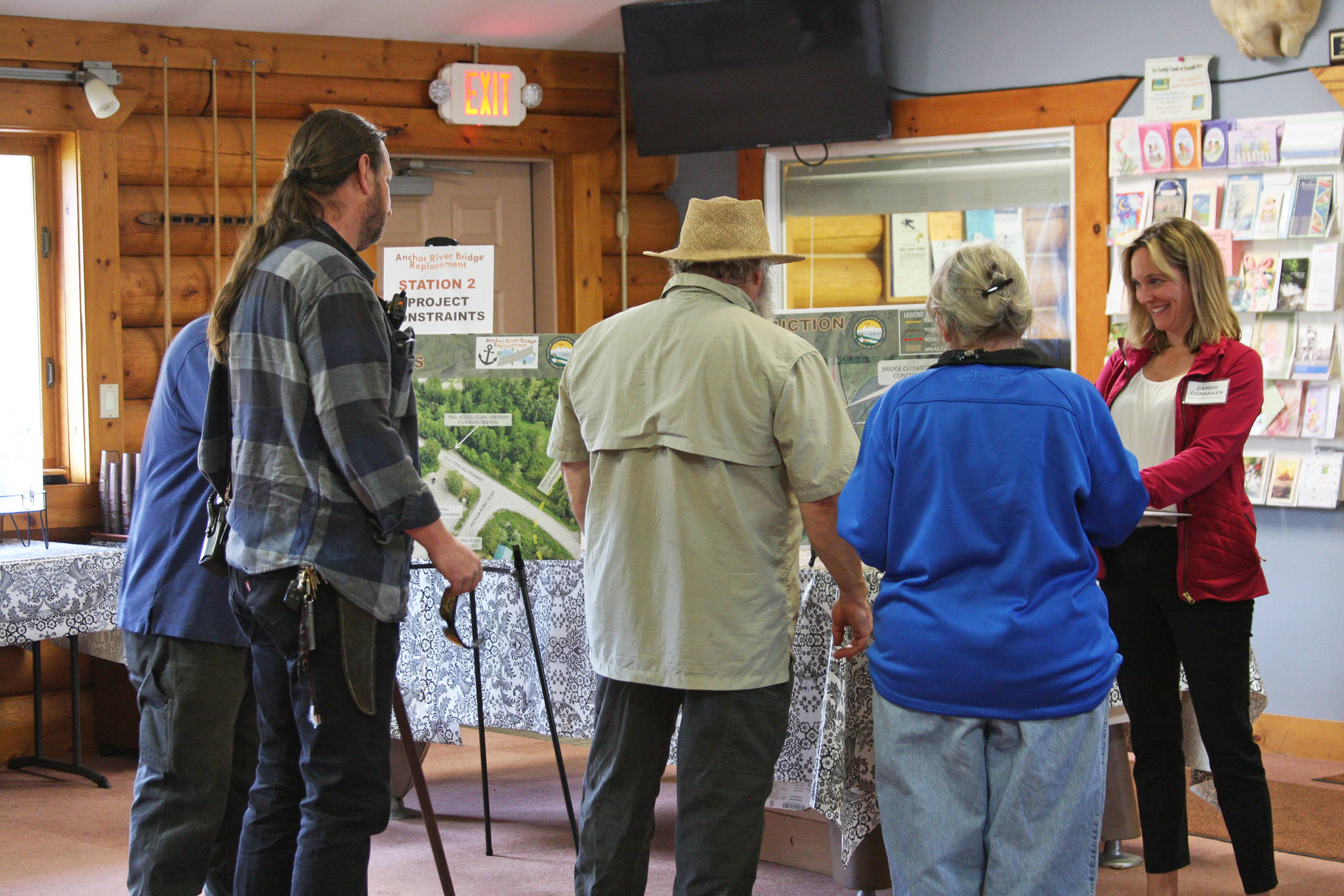 Local Anchor Point residents view the presentation and chat with Carrie Connaker from Solstice Alaska Consulting, Inc., at the open house for the Anchor River Bridge replacement project on Tuesday, Aug. 20, 2019 at the Anchor Point Senior Center in Anchor Point, Alaska. (Photo by Delcenia Cosman)