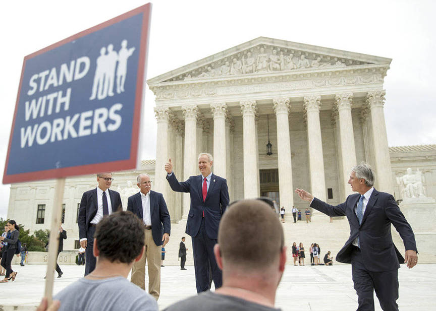 AP Photo | Andrew Harnik                                  Illinois Gov. Bruce Rauner gives a thumbs up outside the Supreme Court in June 2018 in Washington. From left are, Liberty Justice Center's Director of Litigation Jacob Huebert, plaintiff Mark Janus, Rauner, and Liberty Justice Center founder and chairman John Tillman. The Supreme Court ruled that government workers can't be forced to contribute to labor unions that represent them in collective bargaining, dealing a serious financial blow to organized labor.