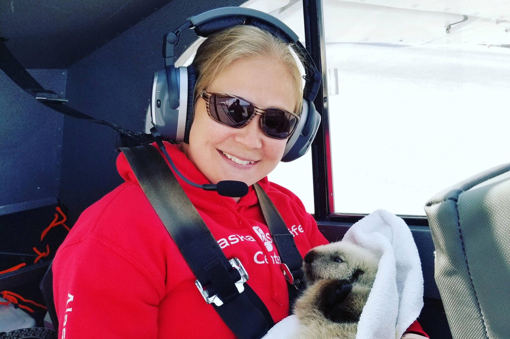 Photo courtesy Alaska SeaLife Center                                  Veterinary Technician Sarah McMillen returns with the sea otter pup in Homer, Alaska, pilot, Duke Marolfs, plane.