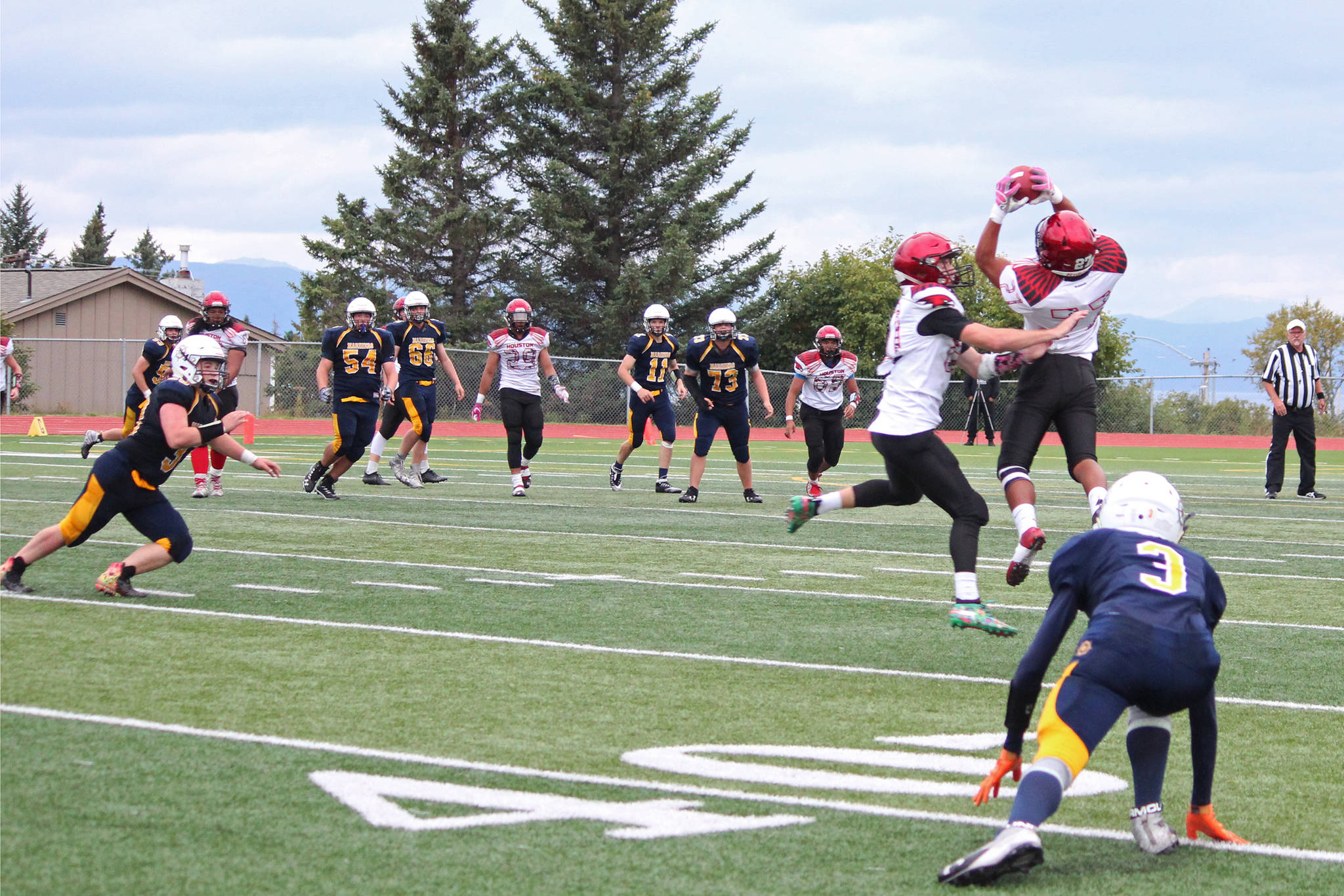 Houston's Apete Sasiu intercepts a pass from Homer's Josh Bradshaw before marking a touchdown during a Friday, Sept. 6, 2019 football game between the two teams at Homer High School in Homer, Alaska. (Photo by Megan Pacer/Homer News)
