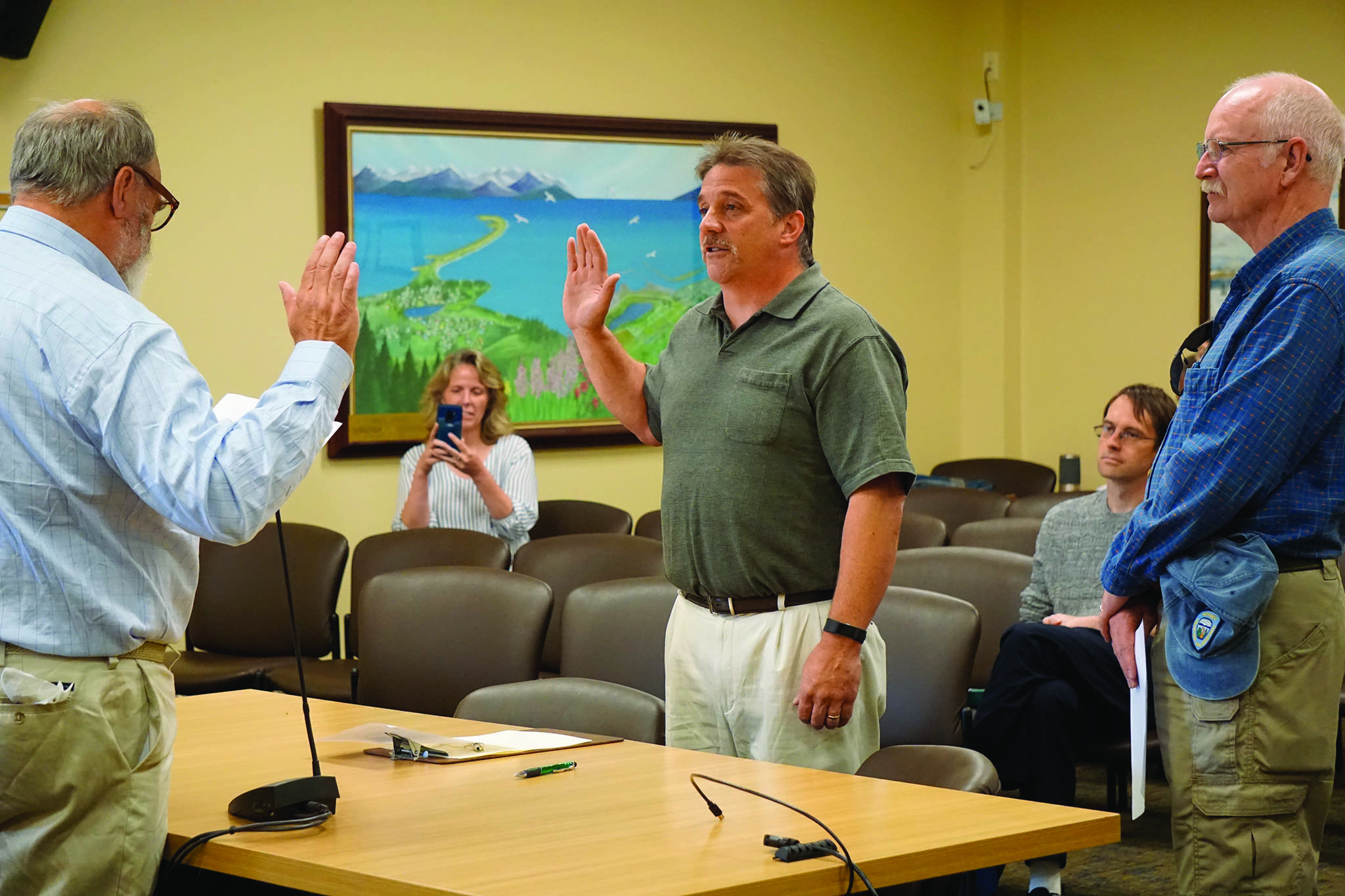Homer Mayor Ken Castner, left, swears in new Homer Volunteer Fire Department Chief Mark Kirko, center, as former Acting Chief Robert Purcell, right, watches at the Homer City Council regular meeting held July 22, 2019, in the Cowles Council Chambers, Homer City Hall, in Homer, Alaska. Castner also read a letter of appreciation Painter, a former HVFD fire chief, thanking him for coming out of retirement to serve as acting chief. (Photo by Michael Armstrong/Homer News)