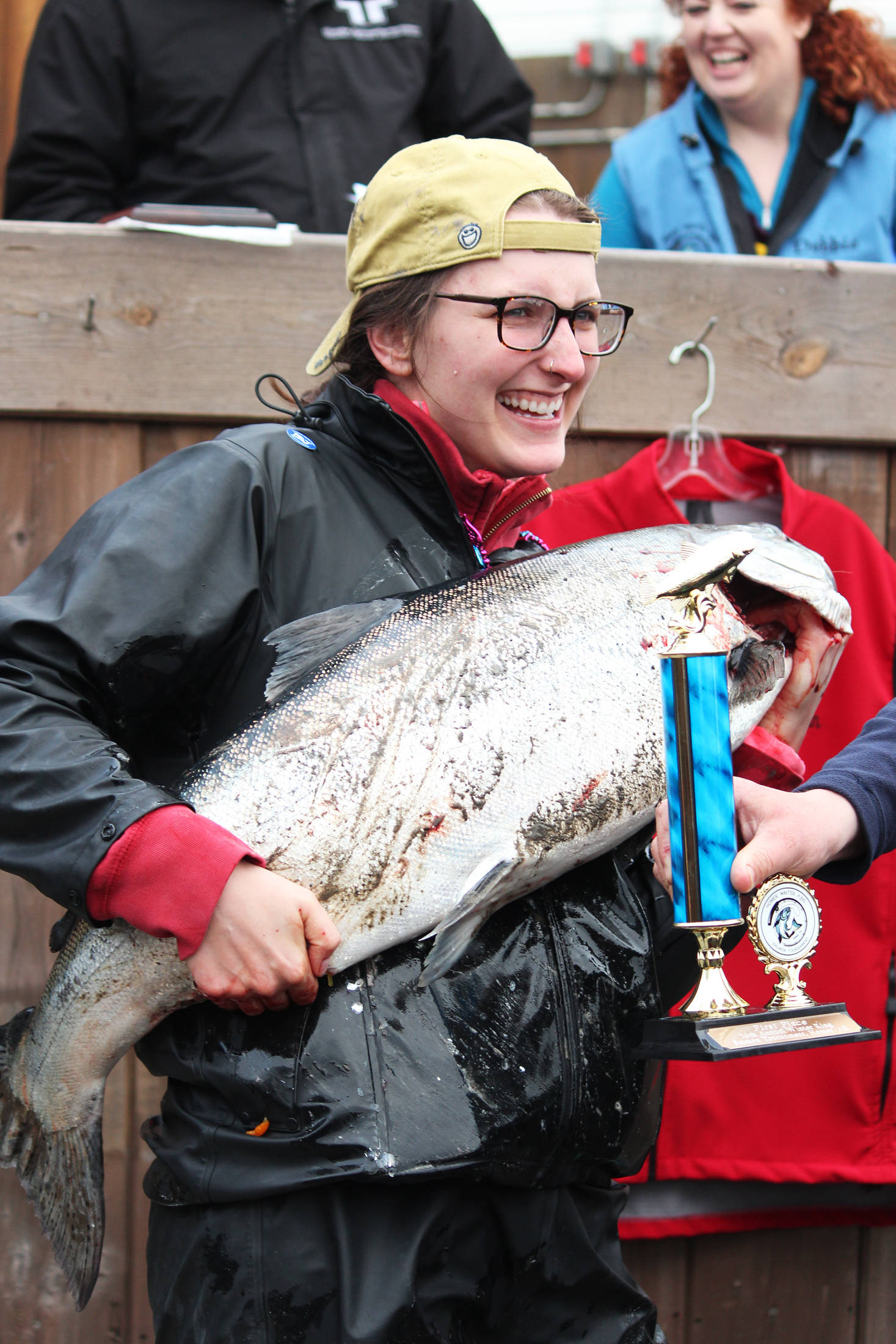 Shayna Perry of Eagle River holds up her 26.7-pound white king salmon while accepting first prize in the Homer Winter King Salmon Tournament on Saturday, March 23, 2019 at Coal Point Seafoods in Homer, Alaska. Perry is the first woman to win the tournament, according to the Homer Chamber of Commerce and Visitor Center. (Photo by Megan Pacer/Homer News)