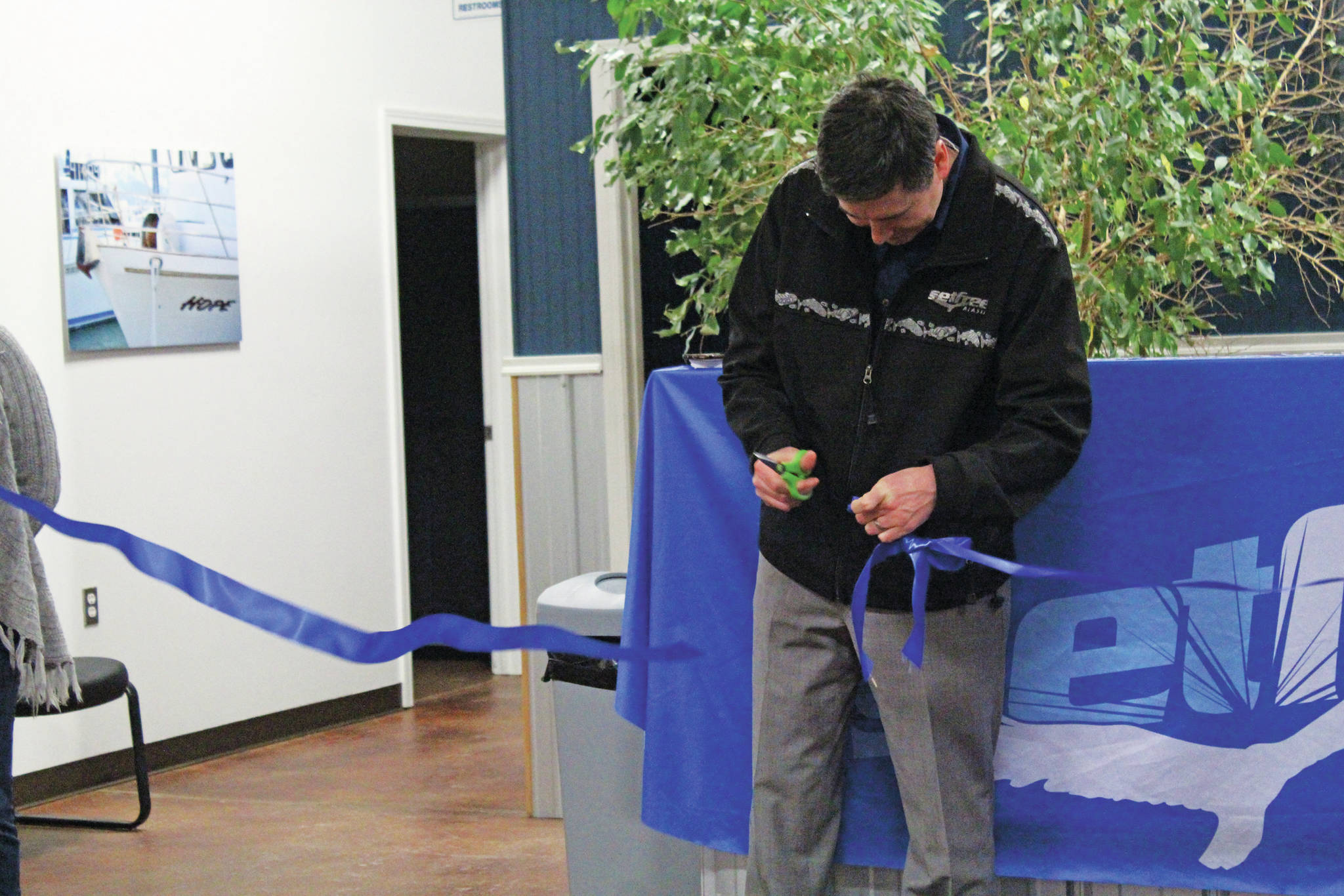 Josh Garvey, a member of Set Free Alaska's board of directors, cuts the ribbon celebrating the opening of the faith-based addiction treatment nonprofit's outpatient services building on Ocean Drive on Monday, Jan. 13, 2020 in Homer, Alaska. (Photo by Megan Pacer/Homer News)