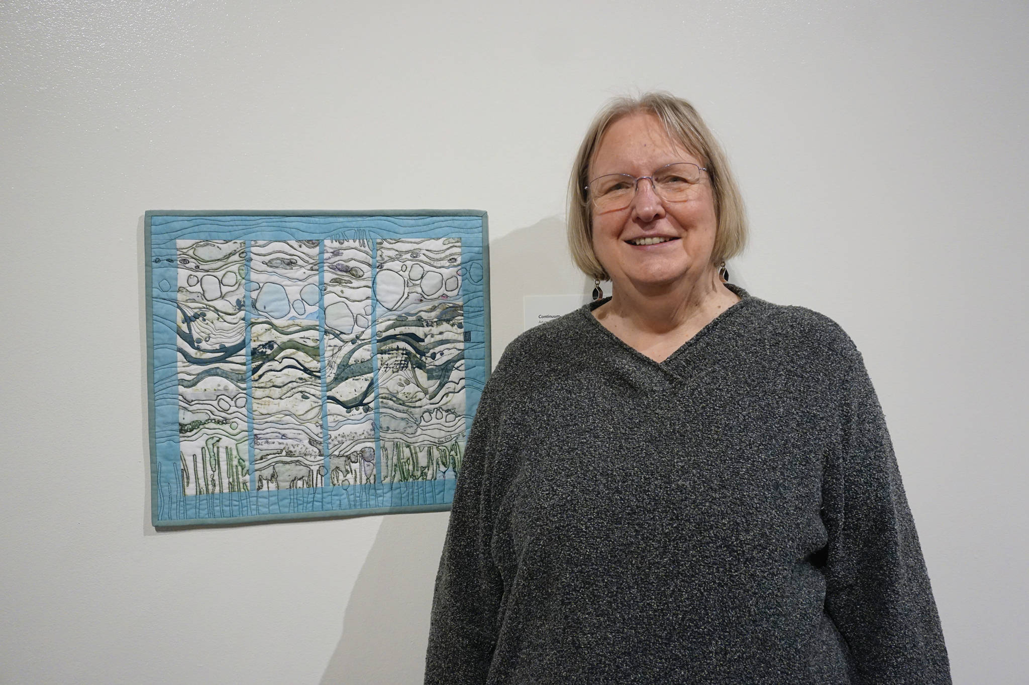 "Ree Nancarrow stands next to her art quilt, ""Continuum"" on Feb. 4, 2020, at the Pratt Museum in Homer, Alaska. It was created in response to composer Libby Meyer's ""Turbulence."" Her work is part of ""Denali Artists Respond to Music Inspired by Wilderness,"" a collaboration between artists and composers showing Feb. 7-May 25, 2020, at the Pratt. (Photo by Michael Armstrong/Homer News)"
