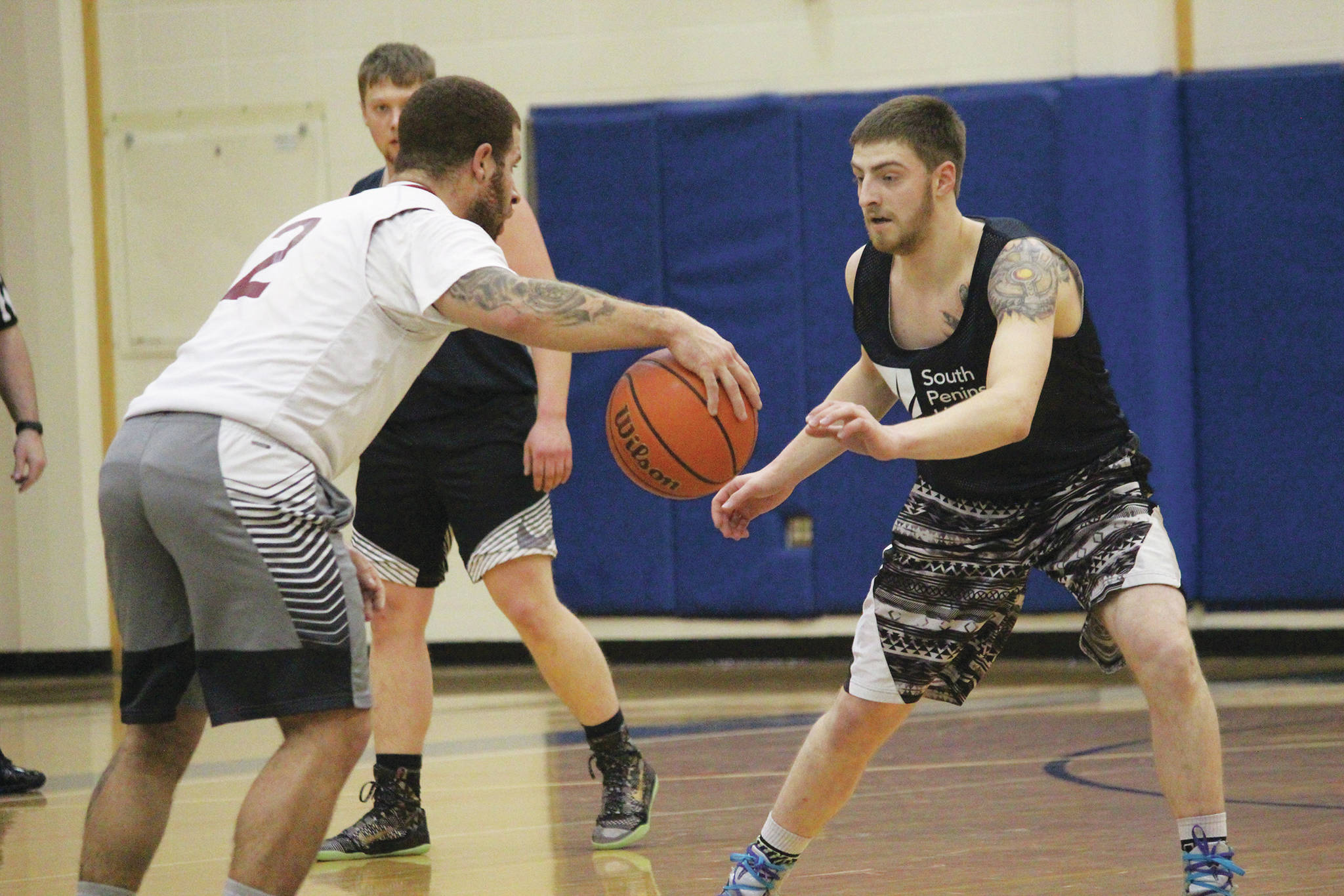Matt Bartolowitz guards Jay Harris during the championship game of the Homer Community Recreation Department's Adult Basketball League Playoffs on Monday, Feb. 17, 2020 at Homer High School in Homer, Alaska. (Photo by Megan Pacer/Homer News)
