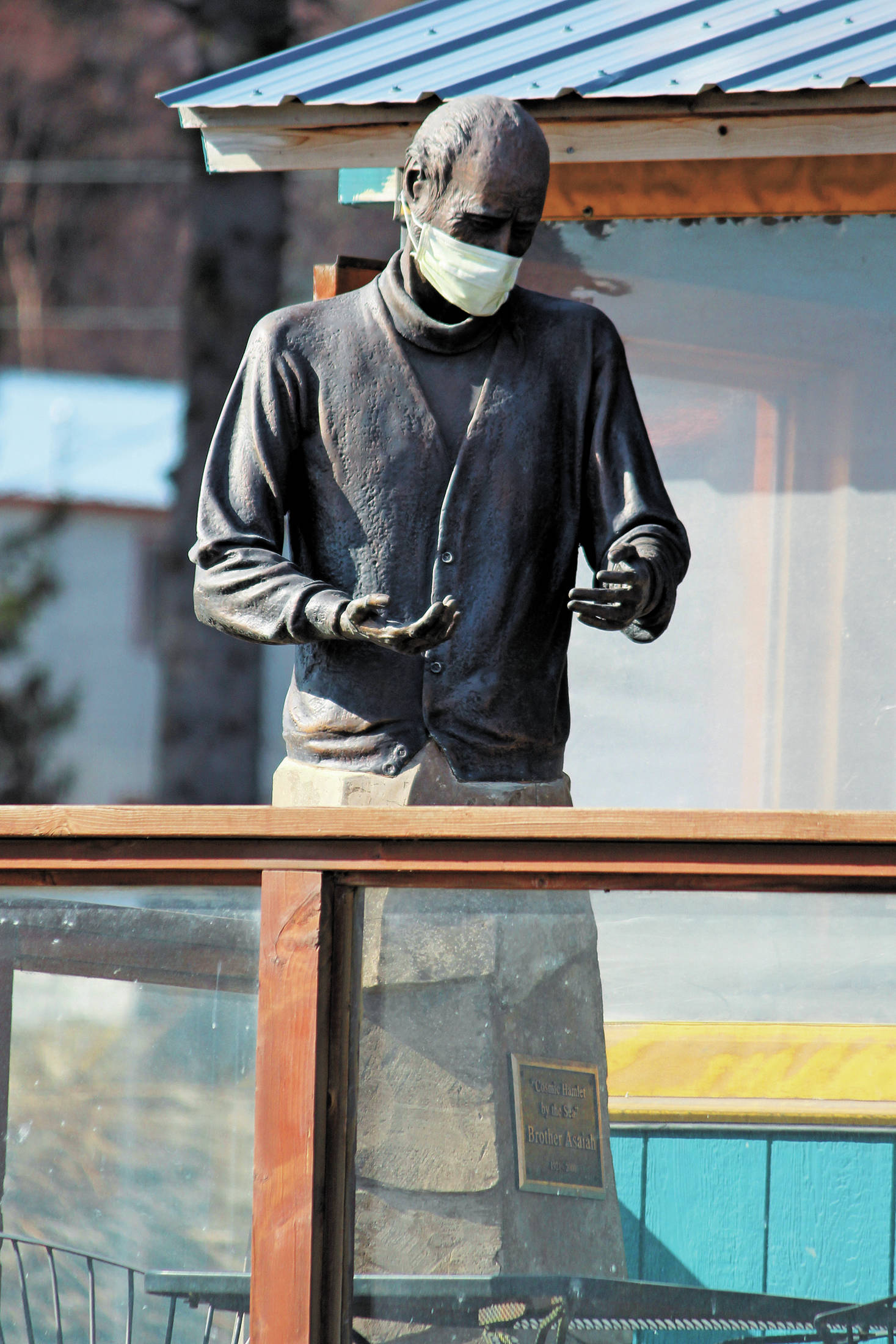 The statue of Brother Asaiah Bates that stands at Cosmic Kitchen is seen wearing a mask on Monday, April 6, 2020 in Homer, Alaska. The state of Alaska is currently advising people to wear protective cloth coverings when they have to go out in public for essentials. (Photo by Megan Pacer/Homer News)