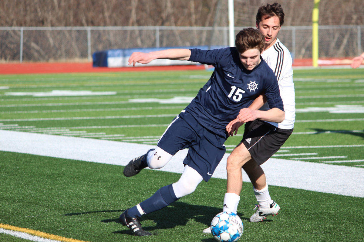 Homer's Ethan Pitzman pushes past Kenai's Thomas Levy-Canedo for possession of the ball during a game on April 16, 2019 at Homer High School in Homer, Alaska. (Photo by Megan Pacer/Homer News)