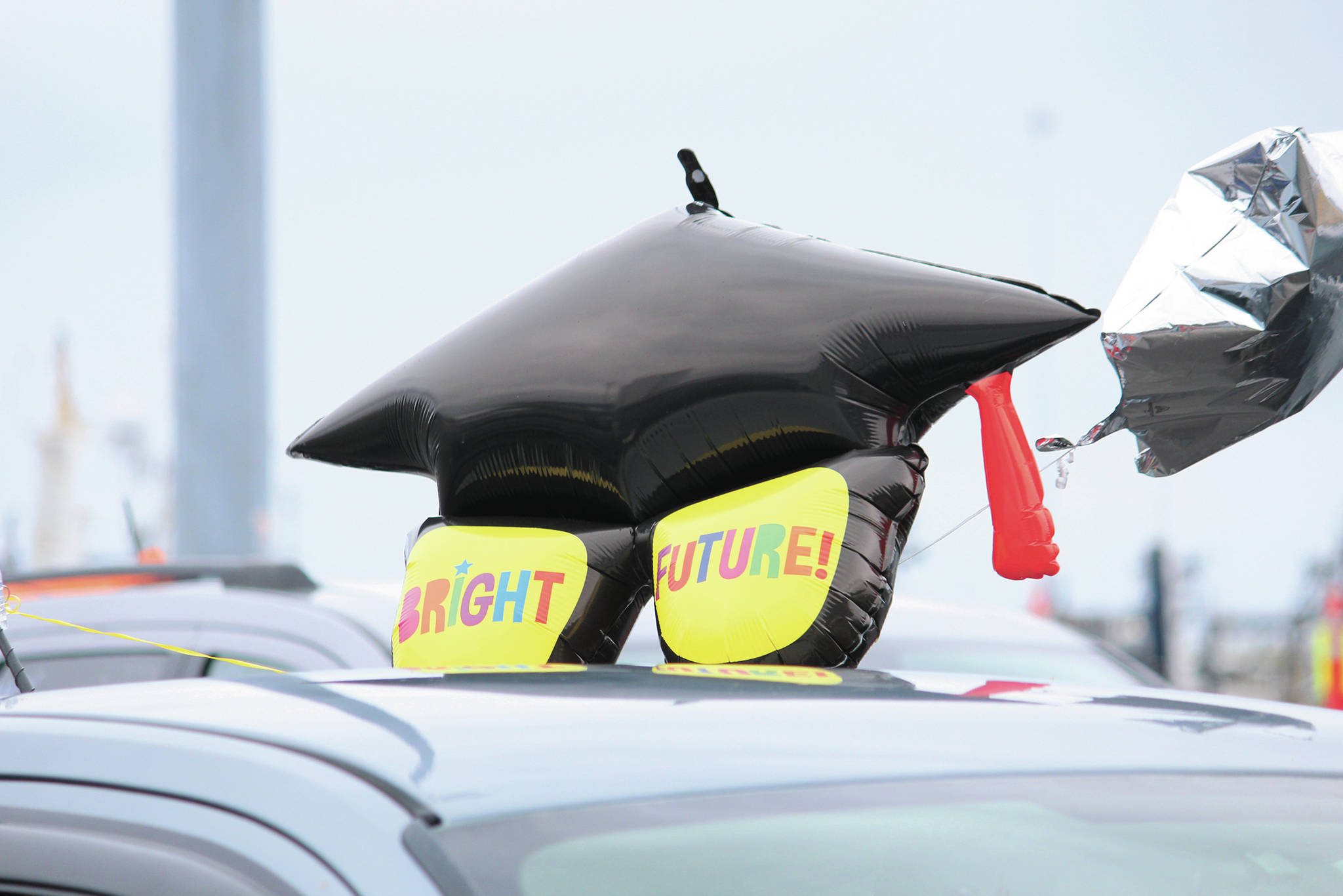 A graduation balloon sits atop a vehicle during an alternative graduation ceremony for Homer Flex School on Monday, May 18, 2020 at the Homer Harbor in Homer, Alaska. (Photo by Megan Pacer/Homer News)