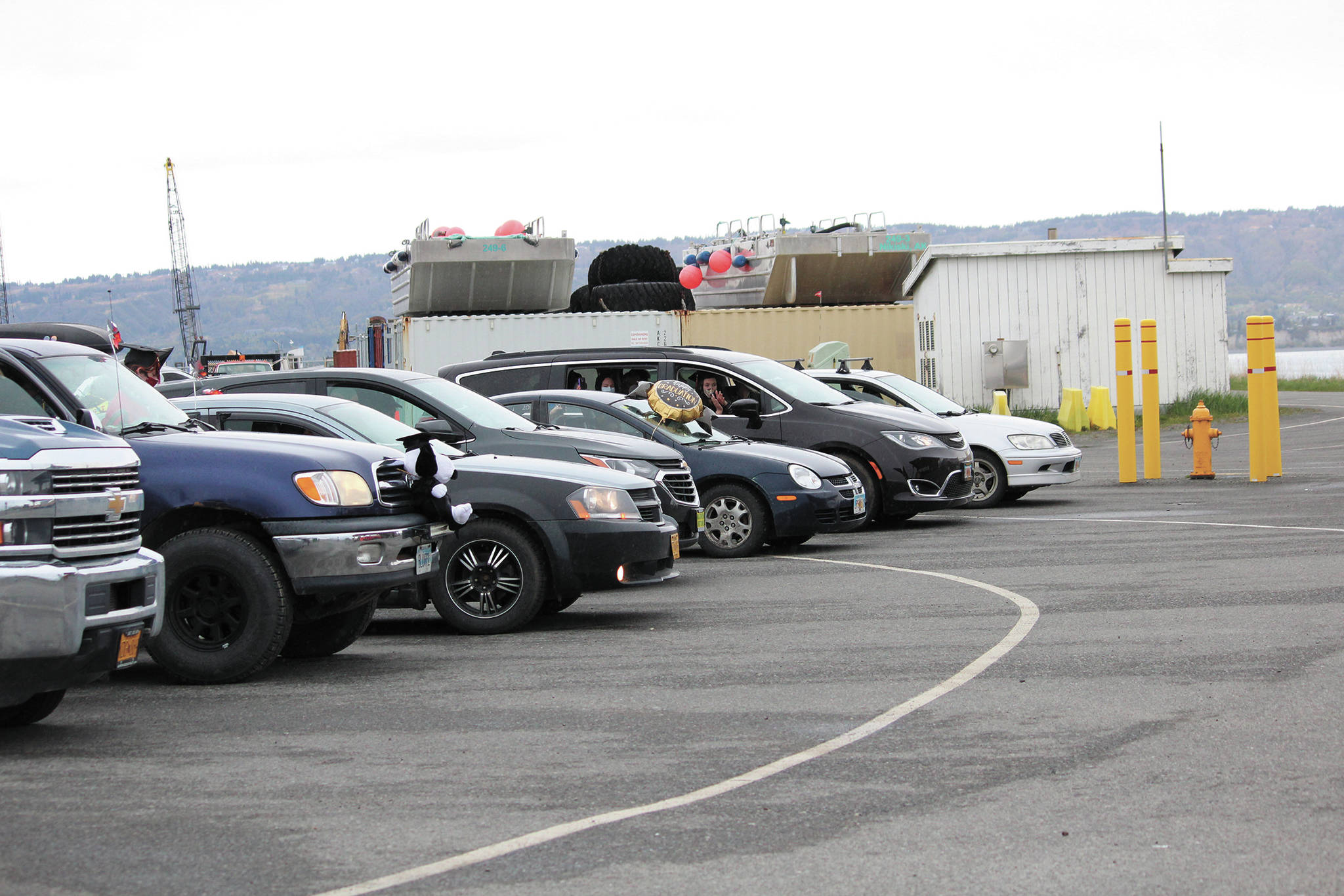 Vehicles wait in line with graduates inside them during a commencement ceremony for Homer Flex School on Monday, May 18, 2020 at the Homer Harbor in Homer, Alaska. Students got out of the vehicles to collect their diplomas and get photos before returning. The program was pre-recorded and played on public radio. (Photo by Megan Pacer/Homer News)