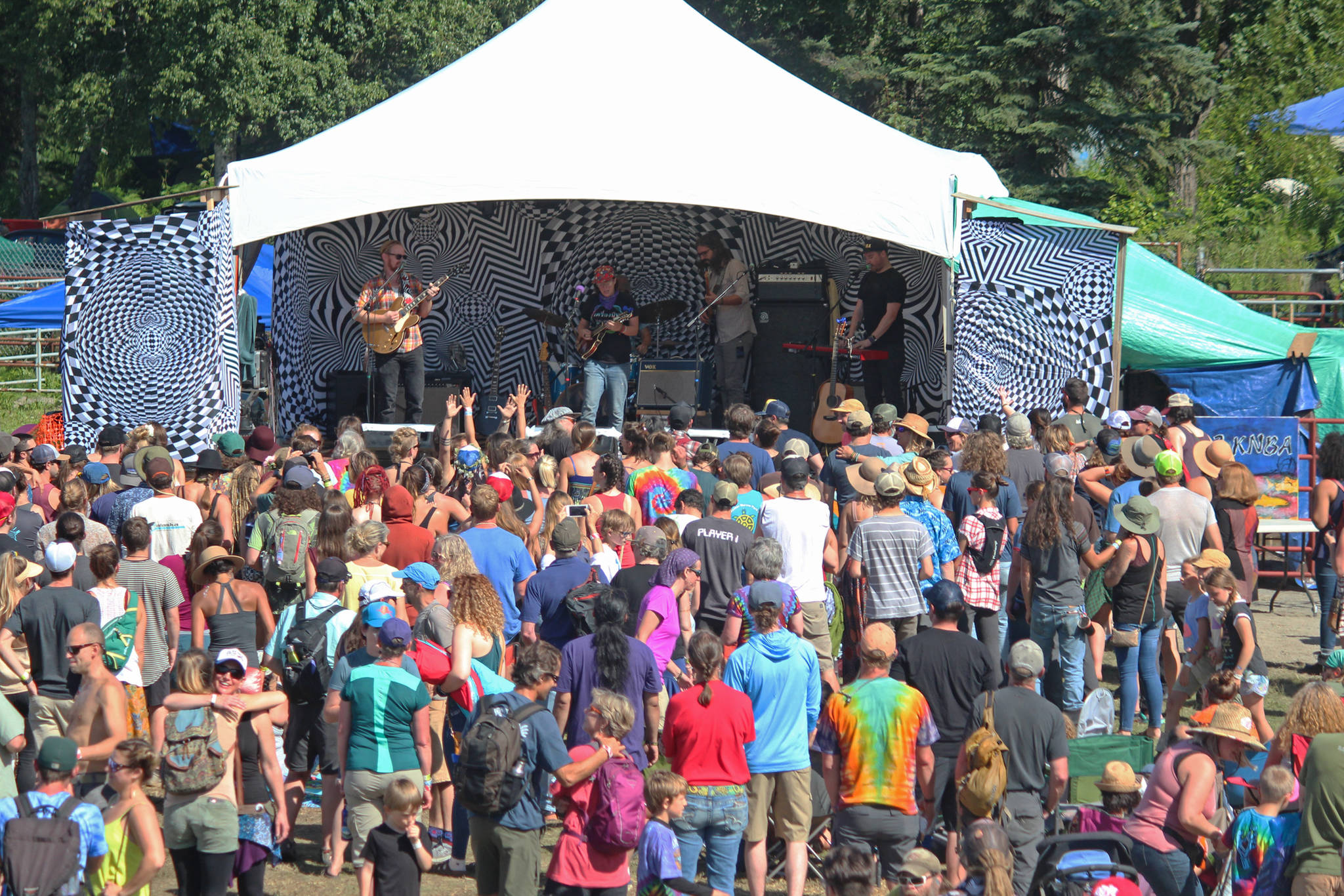 Music lovers listen to a performance on the River Stage at Salmonfest on Saturday, Aug. 4, 2018 in Ninilchik, Alaska. (Photo by Megan Pacer/Homer News)