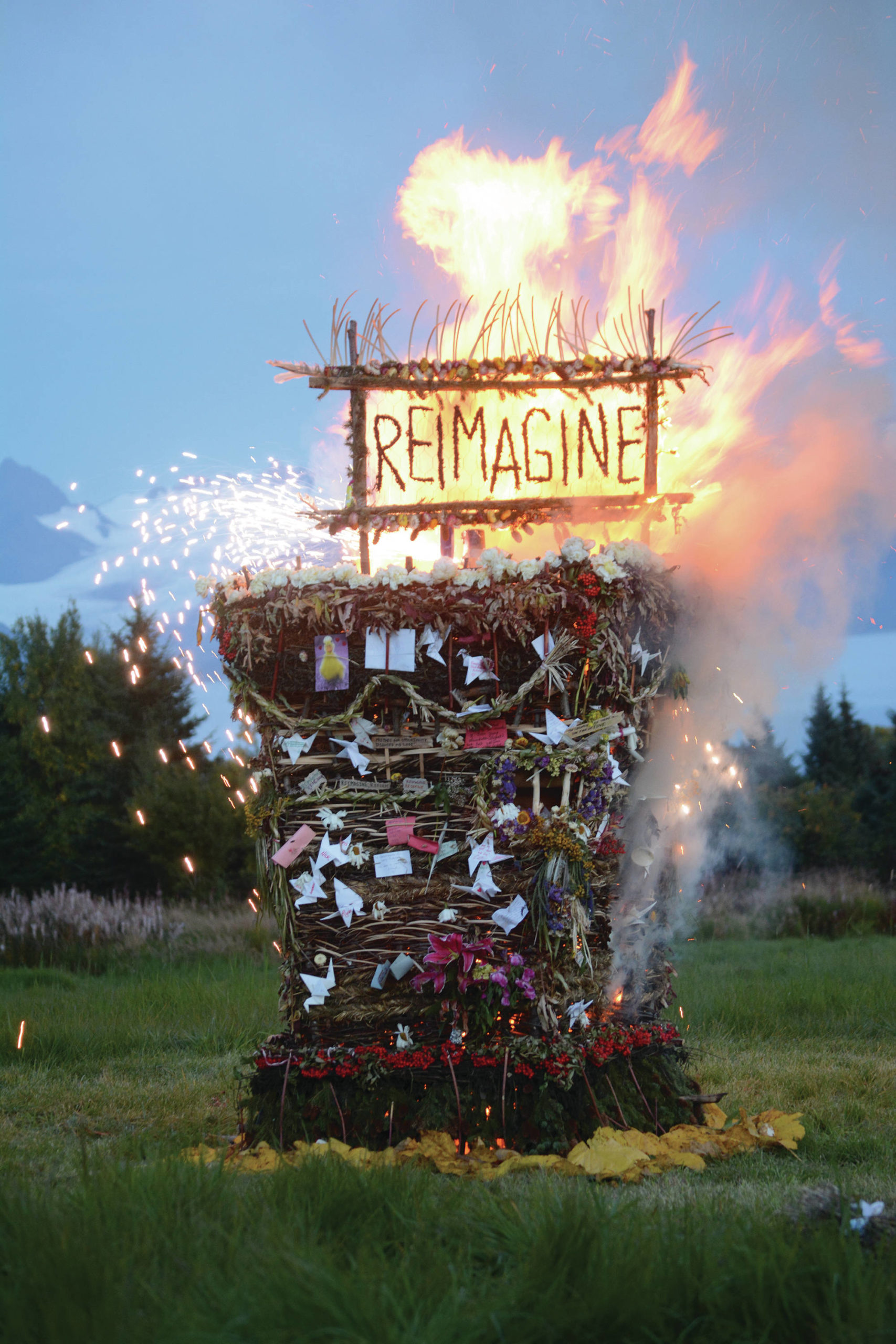 """Reimagine,"" the 17th annual Burning Basket, catches fire in a field on Sunday, Sept. 13, 2020, near Homer, Alaska. Artist Mavis Muller intended to broadcast live on Facebook and YouTube the burning of the basket, but because of technical difficulties that didn't happen. ""Burning Basket teaches how to let go of expectations and accept the present moment,"" Muller wrote in a text message. ""Technology is fickle. The basket, however, did exactly what it promised to do. It helod our collective burderns, our memorials, our joys, sadness, fear, and dispersed all of our good intentions in a plume of smoke, sparks and flames."" (Photo by Michael Armstrong/Homer News)"