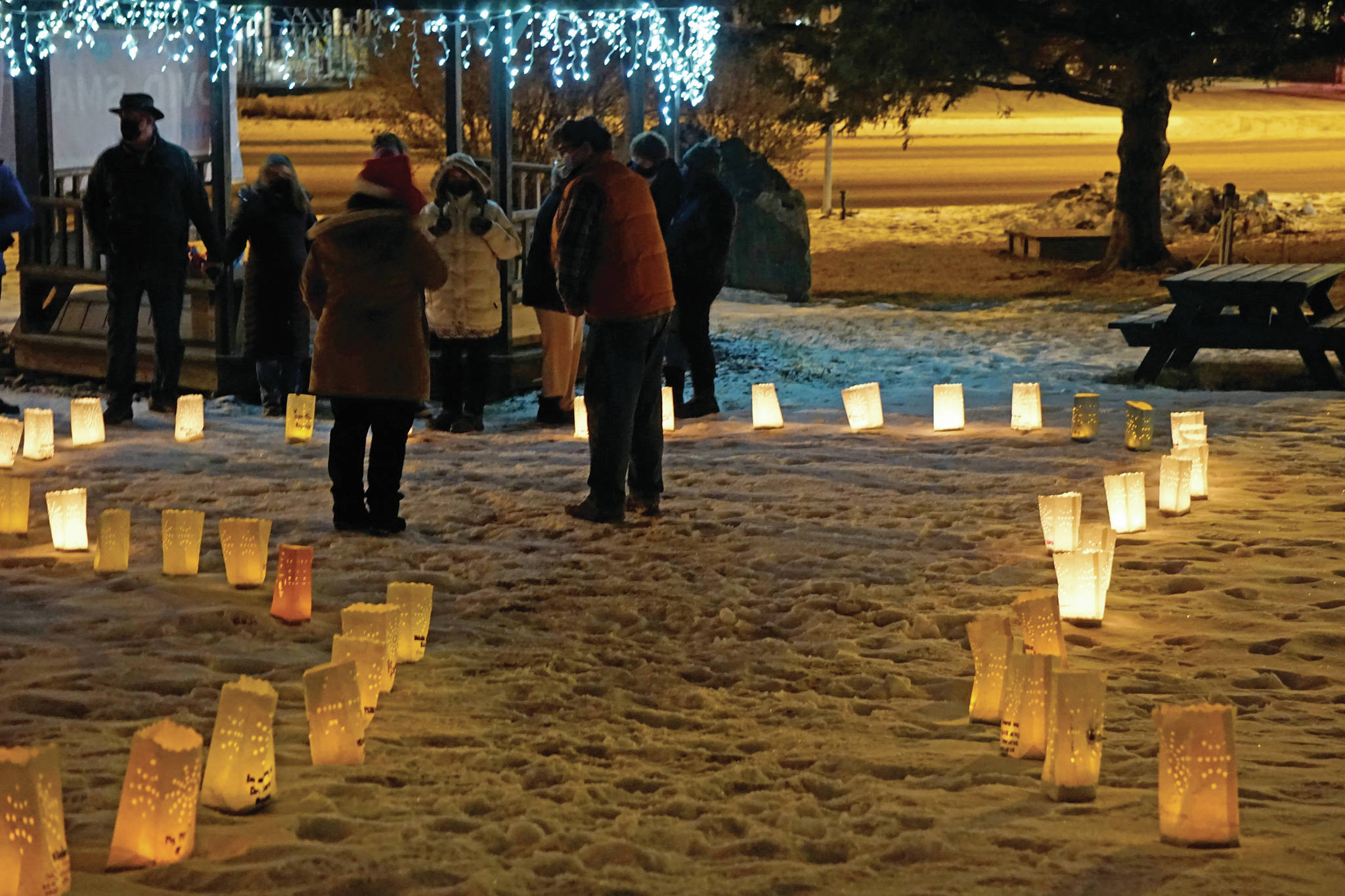 """Memorial luminarias provide a somber light at Hospice of Homer's """"Light Up a Life"""" and 35th Anniversary Gathering last Friday, Dec. 18, 2020, at WKFL Park in Homer, Alaska. The event honored staff and volunteers who have helped out at the organization over the decades. As a fundraiser for hospice, people purchased luminarias to honor deceased friends and family. Luminarias are a Hispanic tradition where candles are placed in a paper bag weighed down with sand. Also known as farolitios, Catholics place luminarias to guide the spirit of the Christ child to one's home. (Photo by Michael Armstrong/Homer News)"""